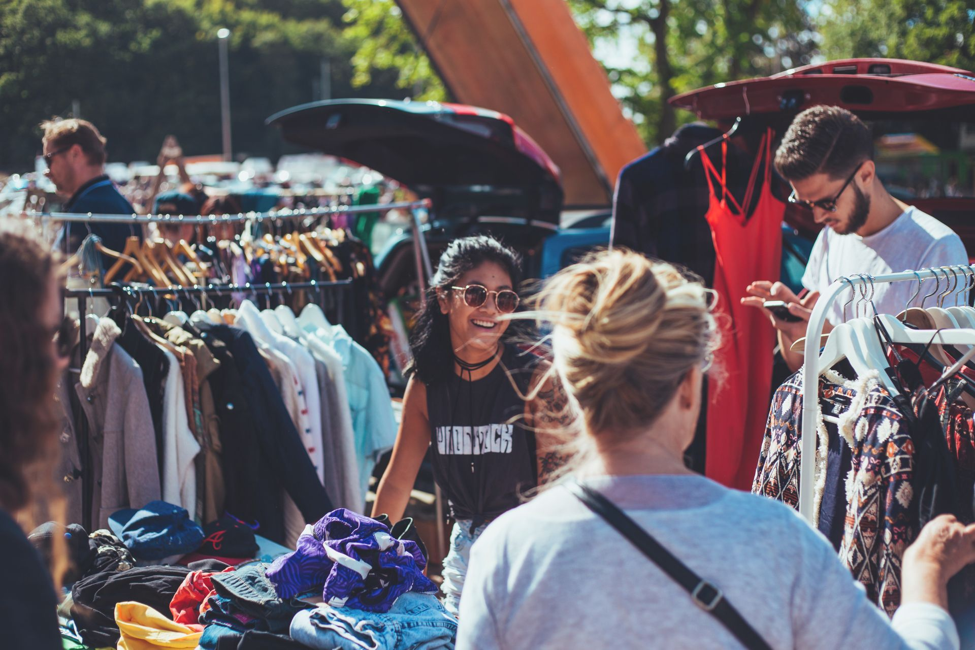 People browsing through racks of clothing at outdoor flea market