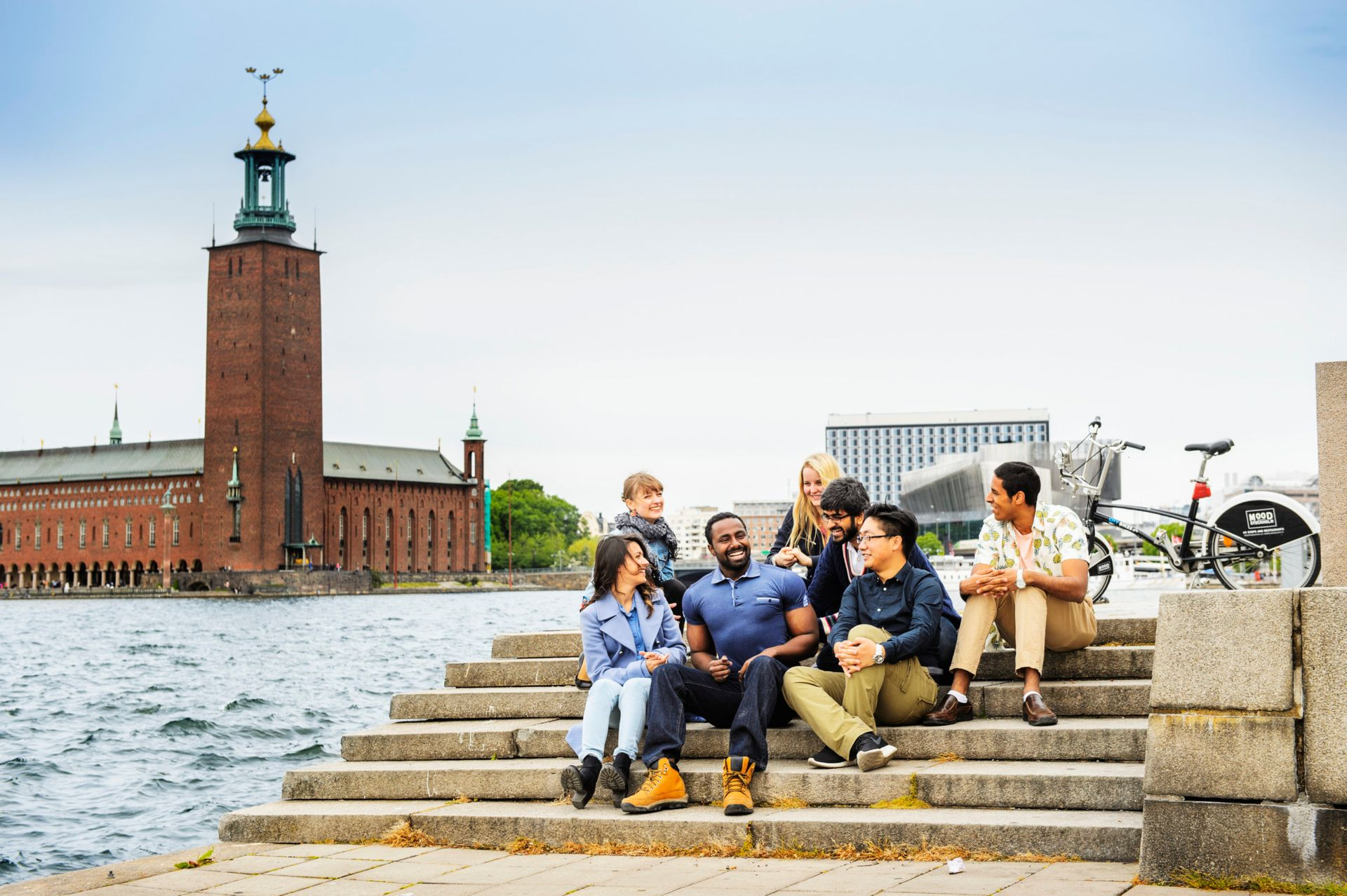 A group of international students sitting on steps outside. The Stockholm city hall is in the background.