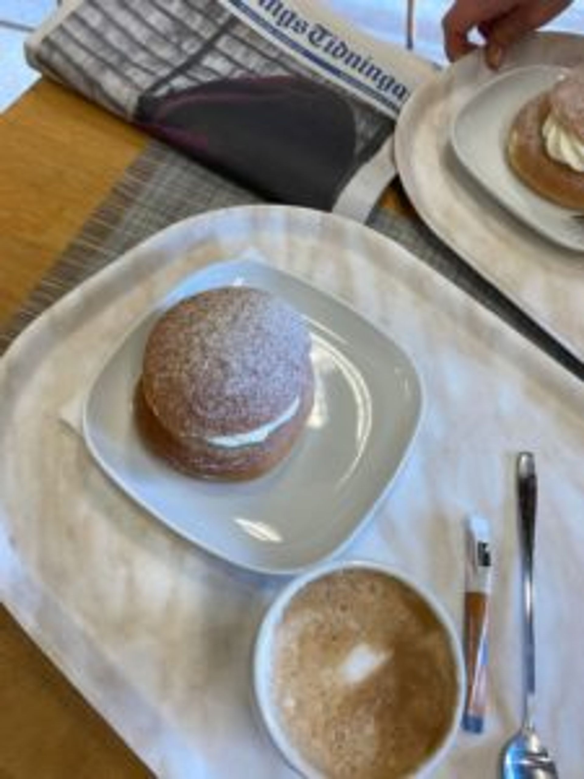 A tray with a cup of coffee and a semla - a traditional Swedish pastry.