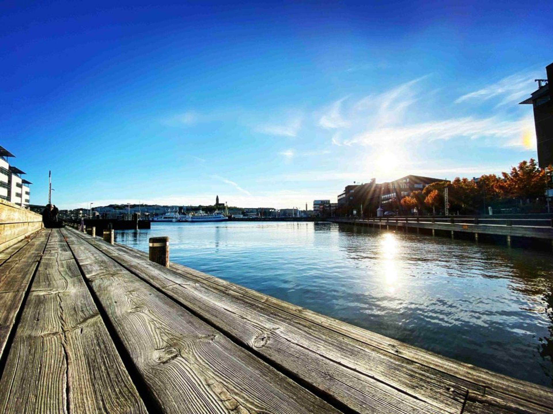 People sitting on a boardwalk beside the sea in Gothenburg.