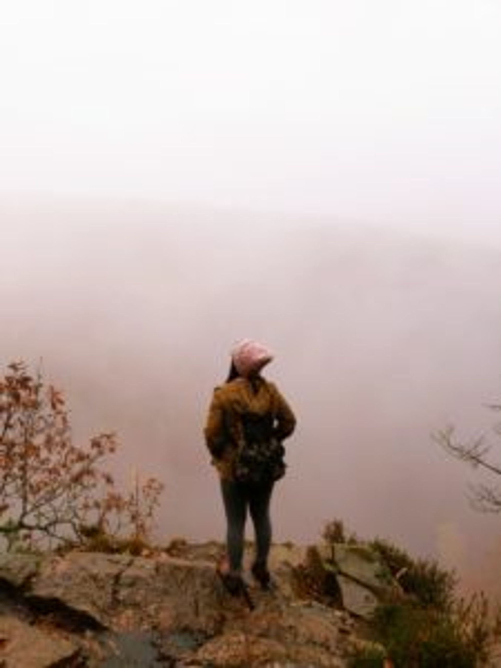 Nguyên standing on a cliff looking out over a misty valley.