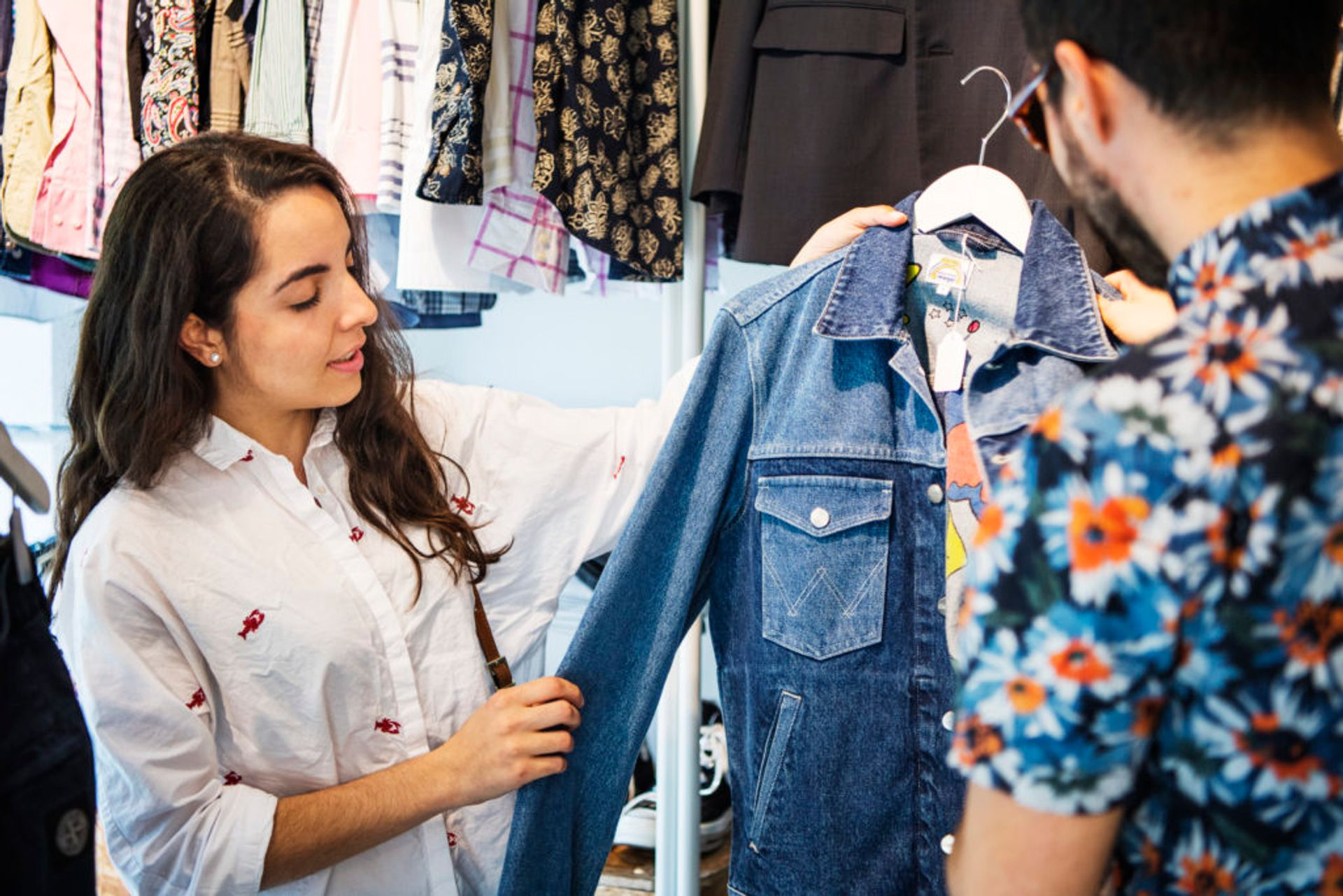 Two people in a second hand shop looking at a denim jacket.