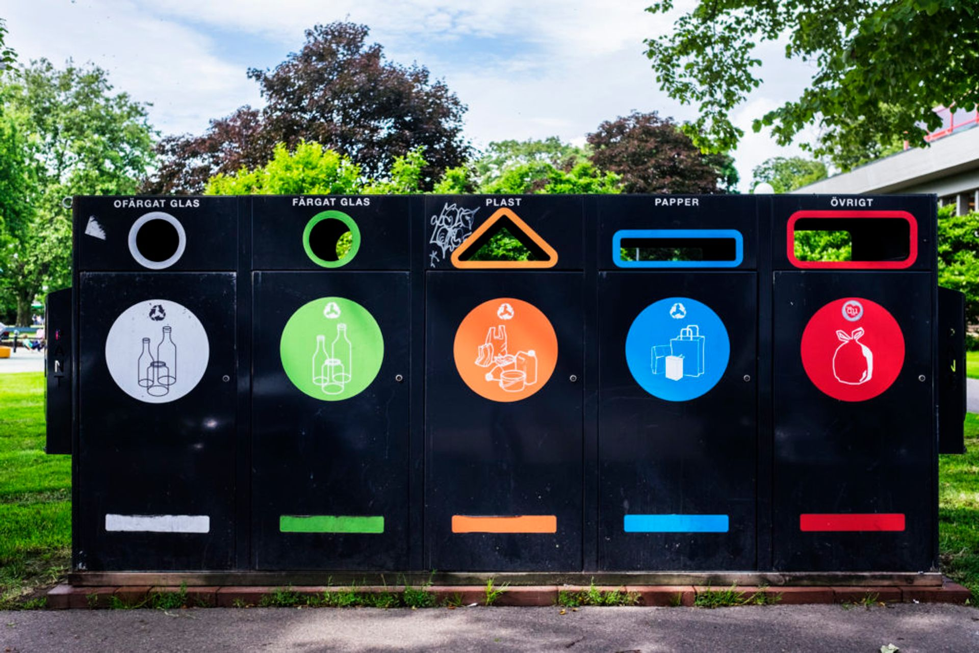 Recycling station for plastics, paper, coloured glass and clear glass outside a residential building.