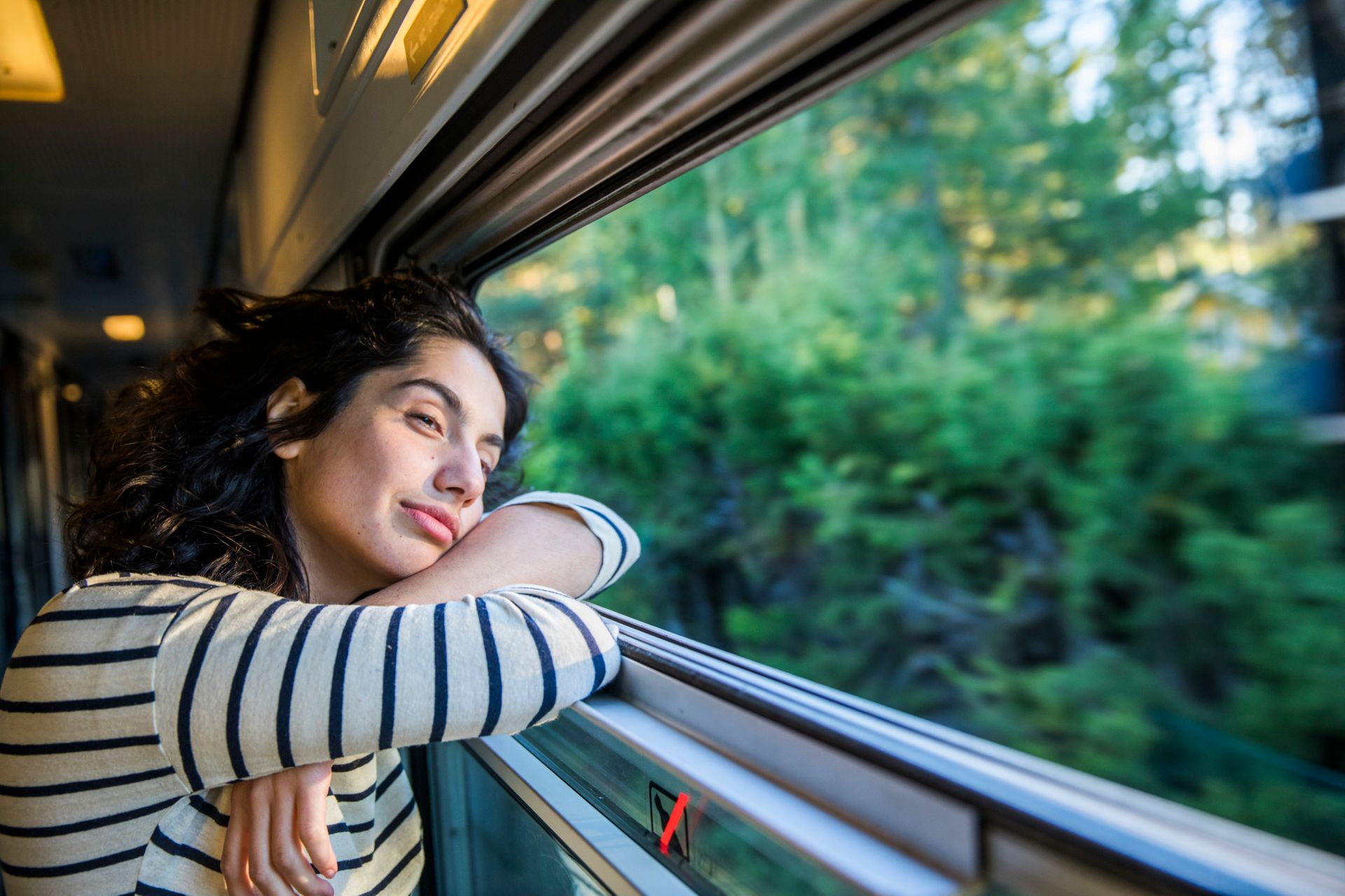 A dark-haired woman wearing a stripy top staring out of a train window.