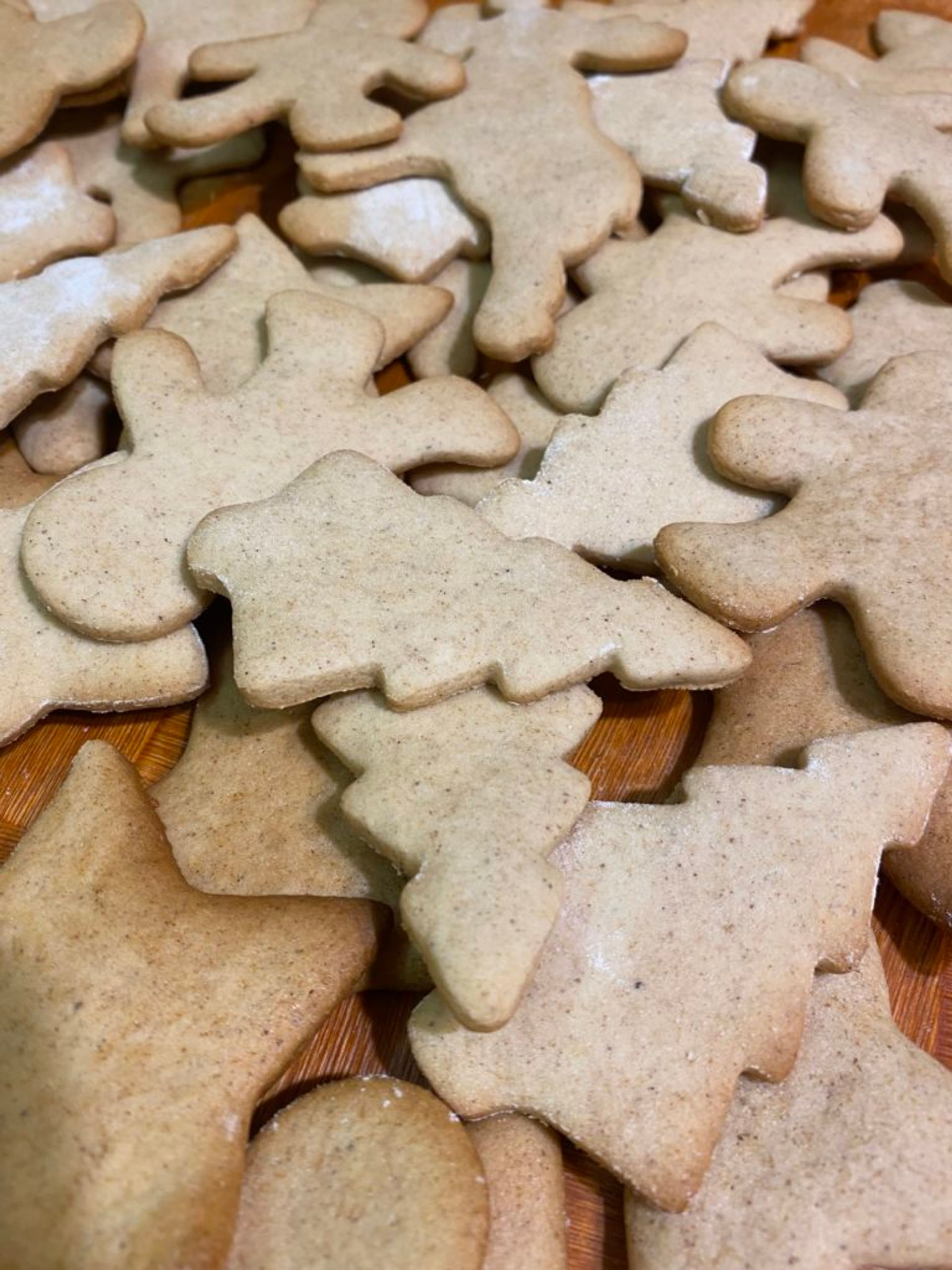 A tabletop covered with freshly baked gingerbread cookies in the shape of people and Christmas trees.