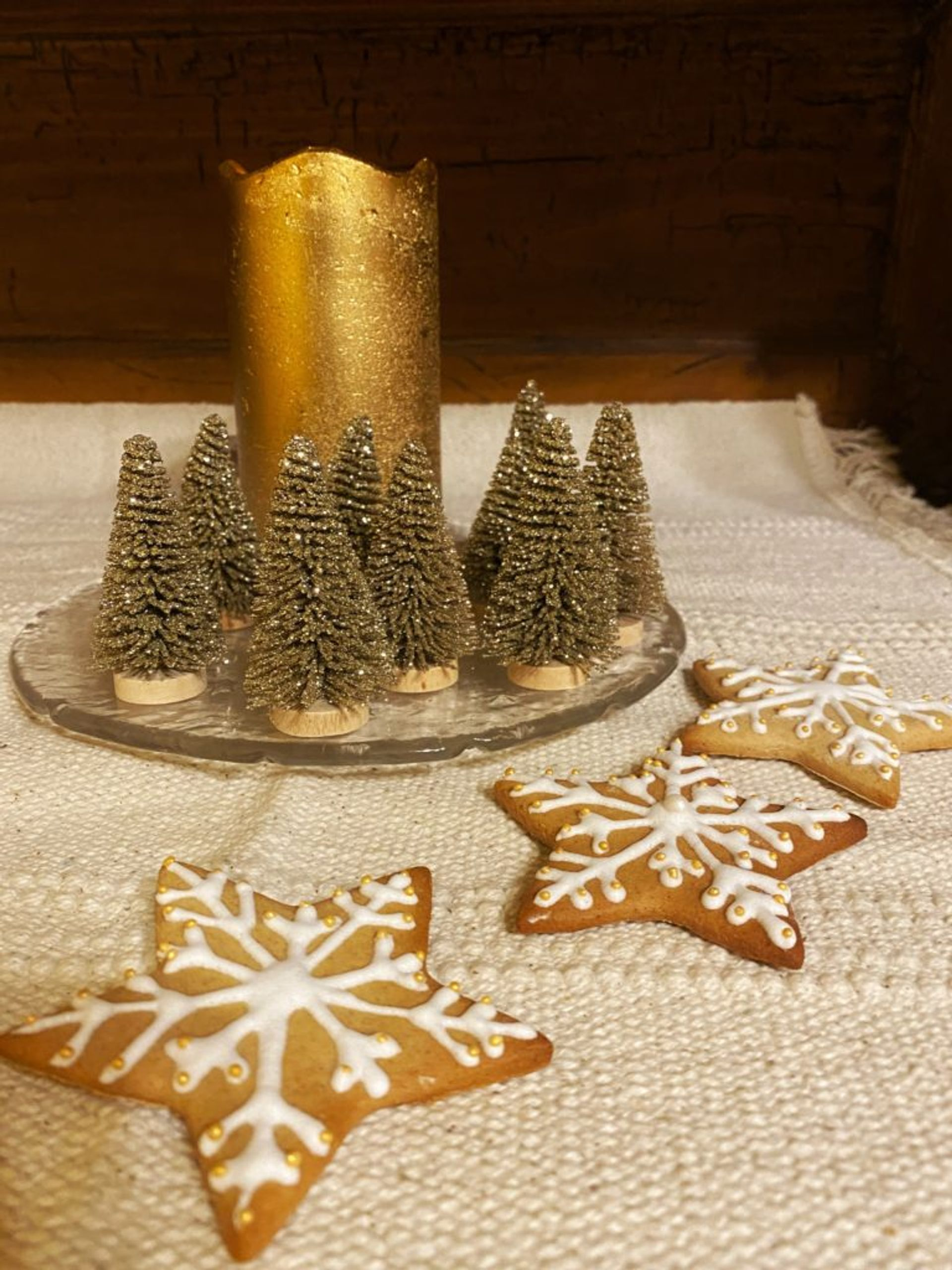 Three gingerbread cookies in the shape of stars decorated with white icing.