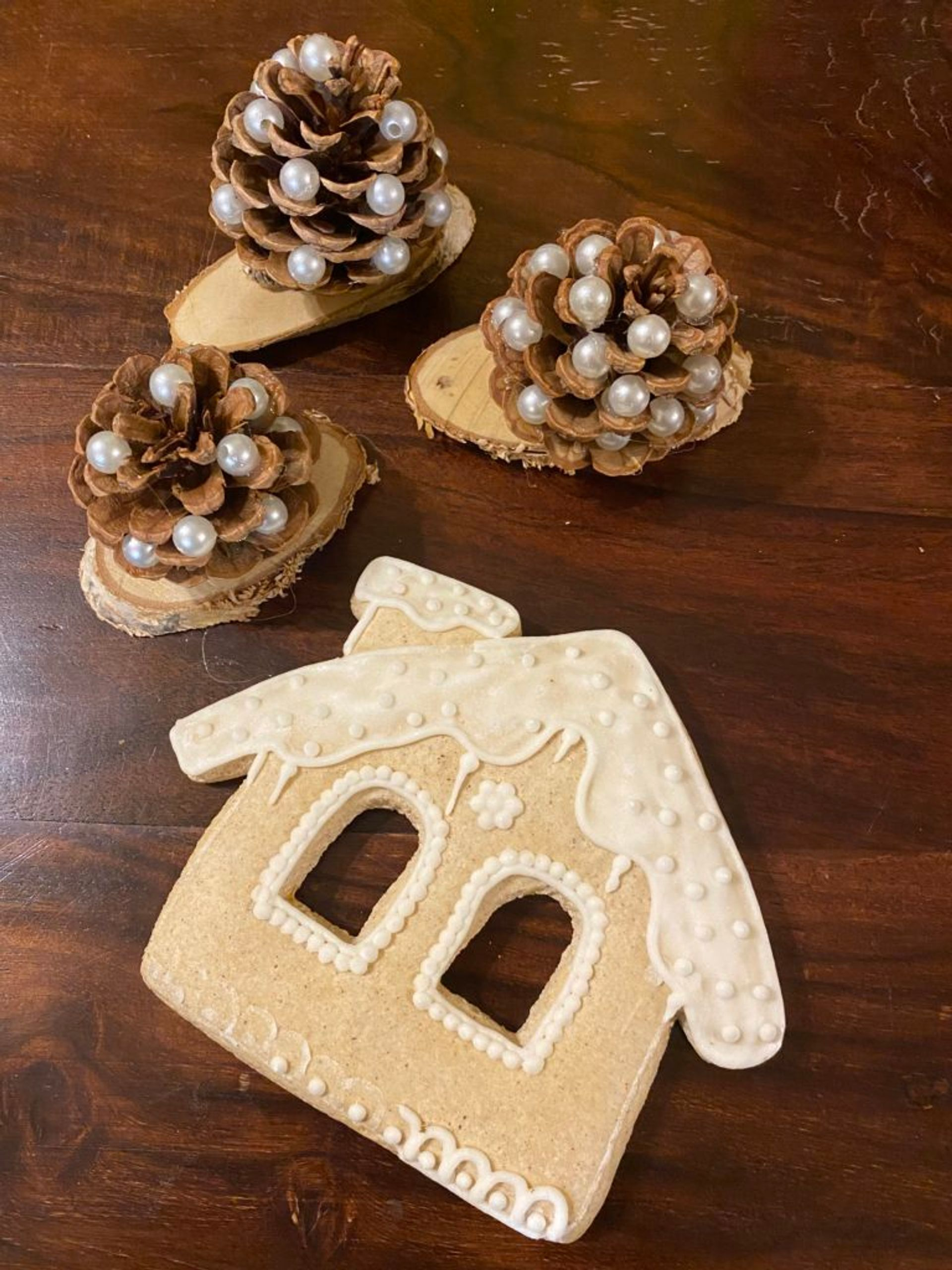 A gingerbread cookie in the shape of a house decorated with white icing.