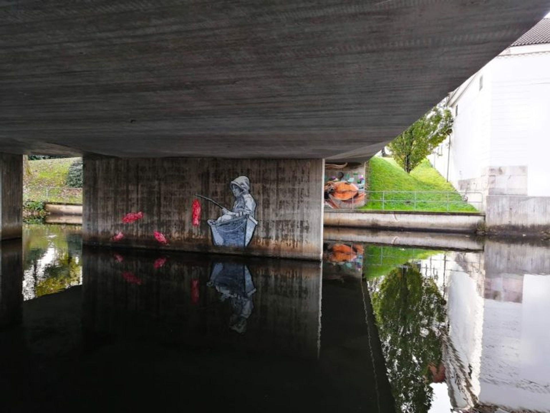 Mural of a child fishing in a boat painted on the side of a concrete pile of a bridge in Borås.