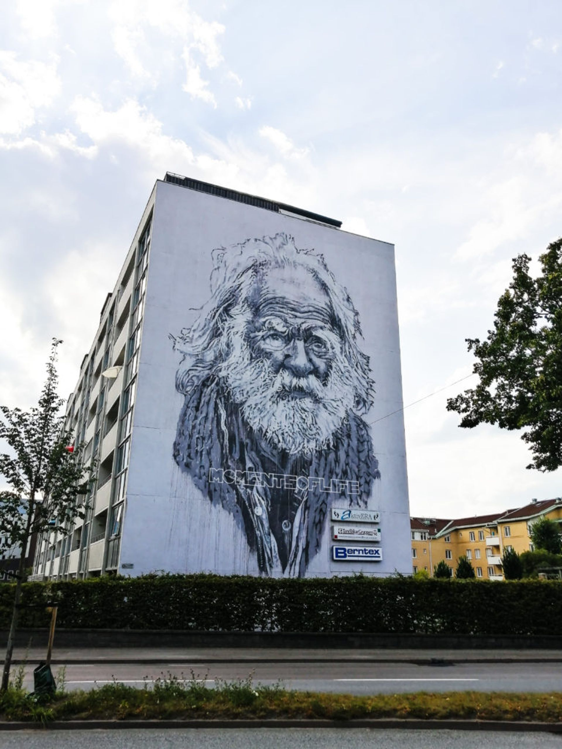 Realistic black and white mural of elderly man with text 'Moments of Life' on the side of a residential building in Borås.