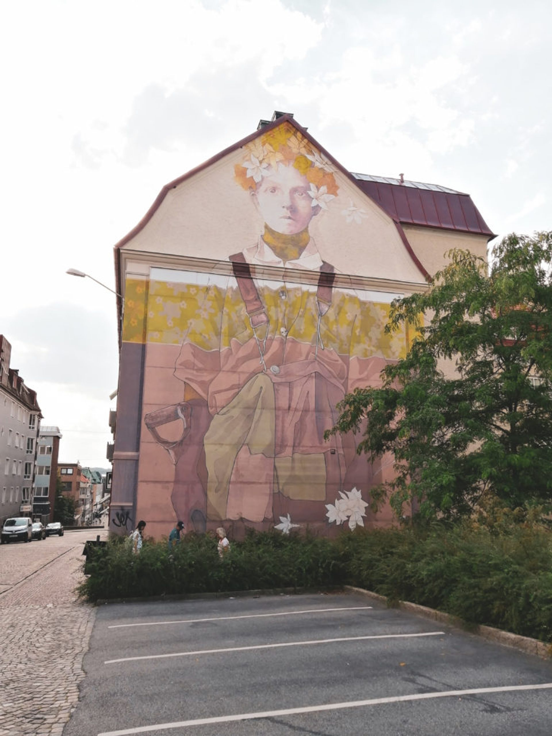 Washed out mural of person wearing dungarees and flower crown on the side of a residential building.