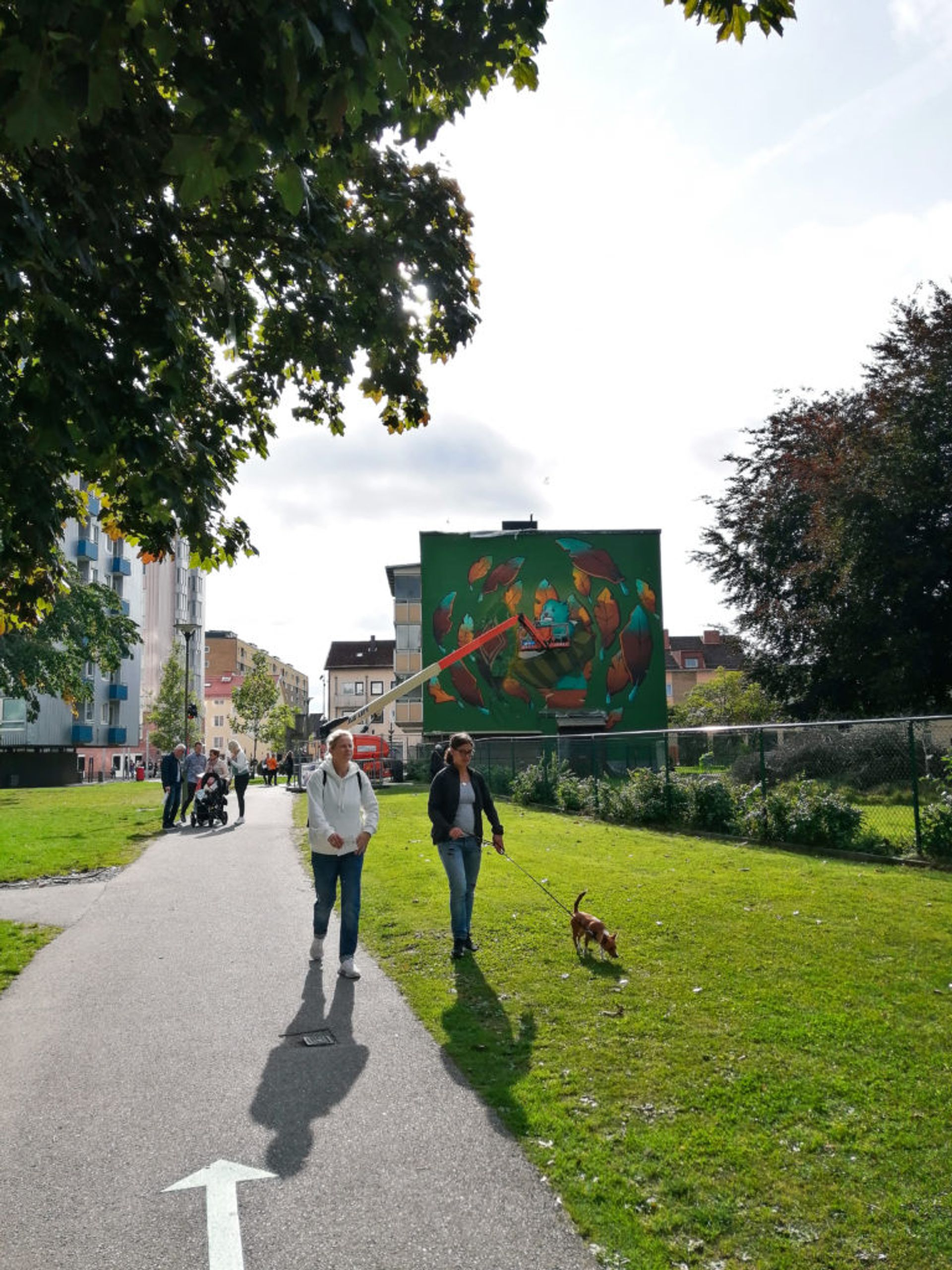 Women walking a dog in front of a mural being painted in Norrby.