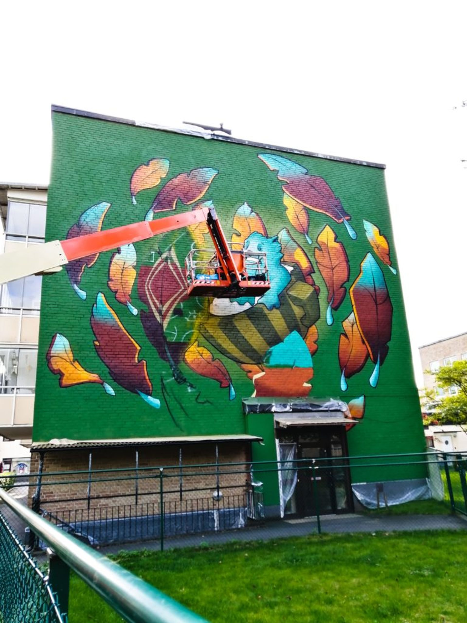 Colourful and animated mural of character riding a teacup surrounded by glowing leaves on the side of a building.
