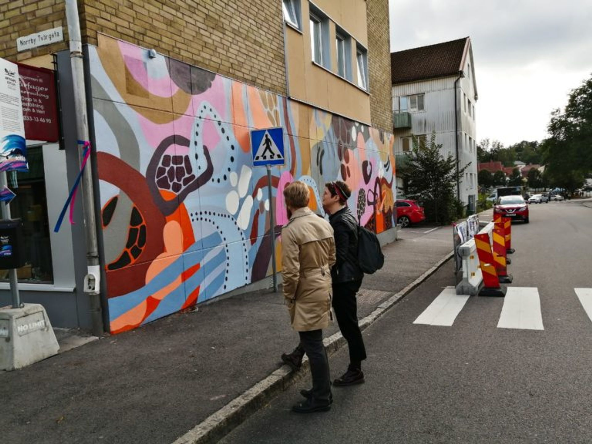 Two men standing and looking at a mural in Borås.