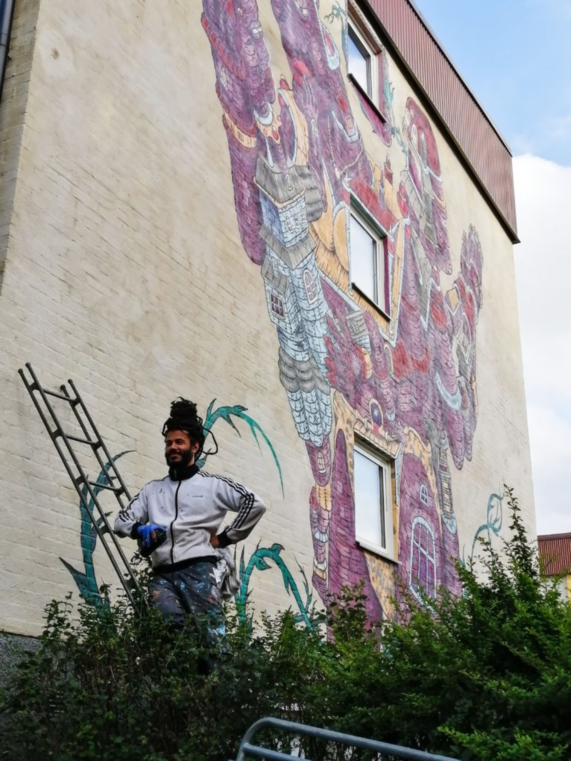 An artist stands on a ladder in front of the mural he is painting.