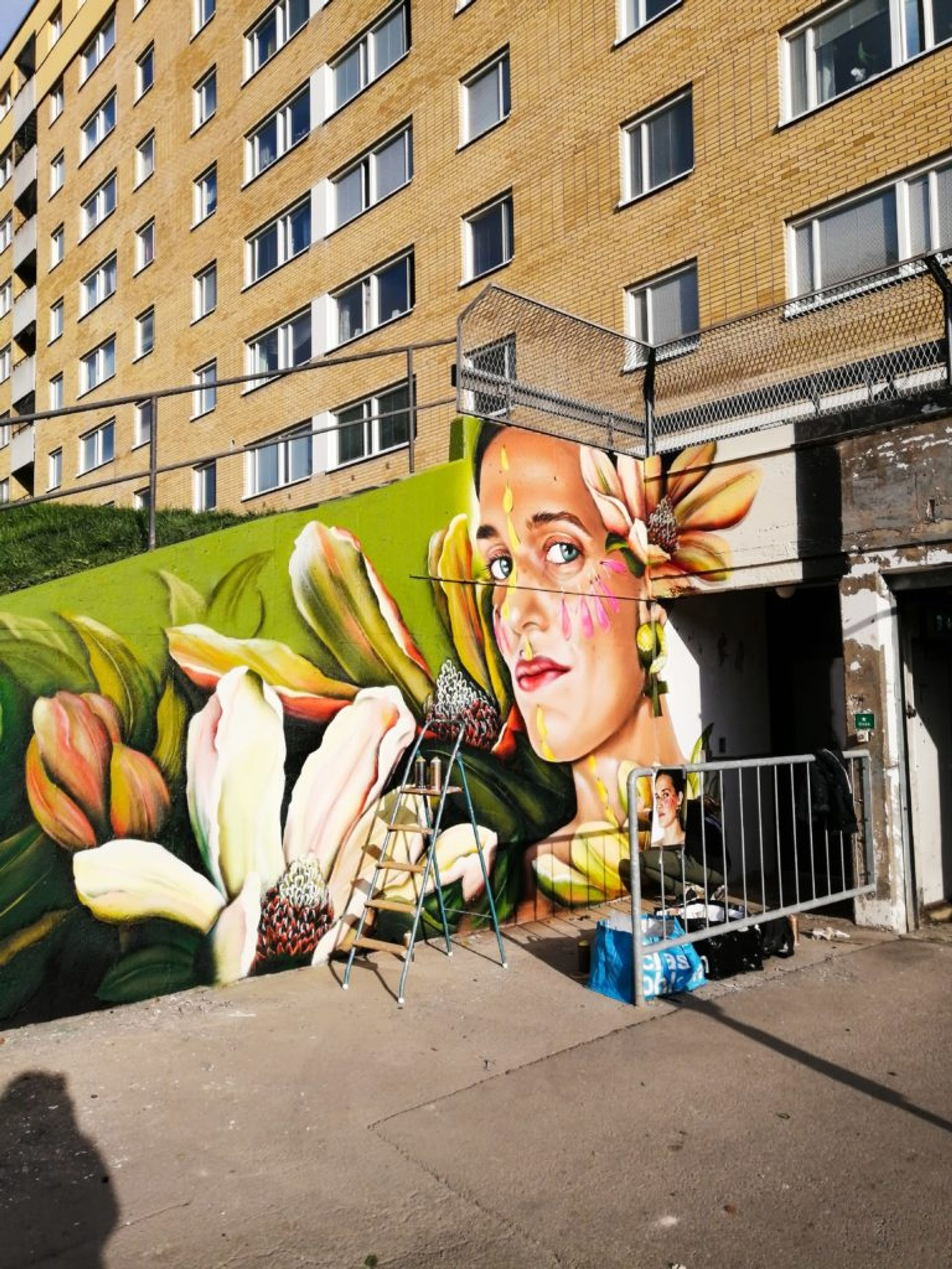 Photorealistic portrait of woman surrounded by flowers on a concrete wall.