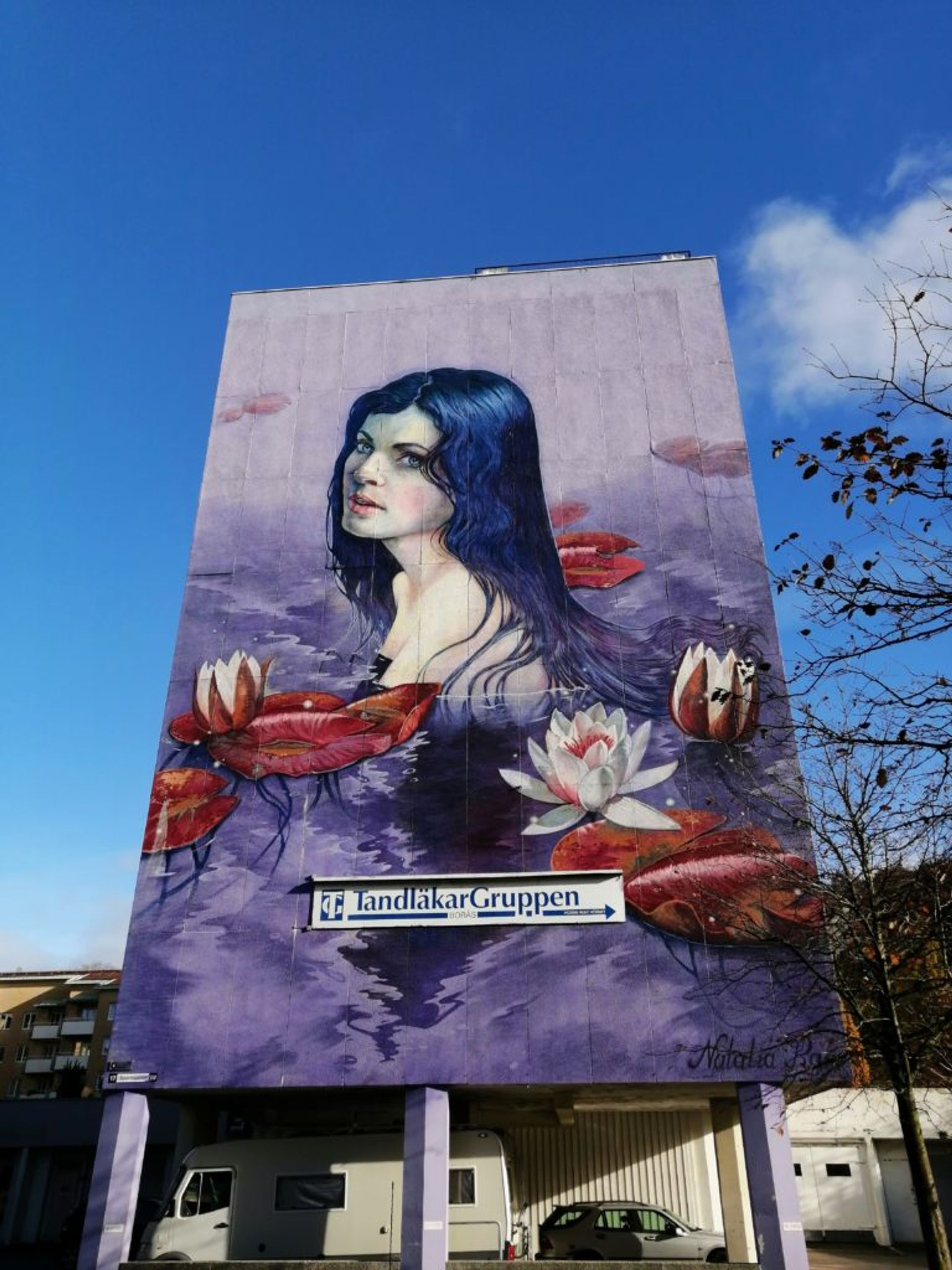 Mural of a woman swimming in purple and blue water on the side of a residential building in Borås.