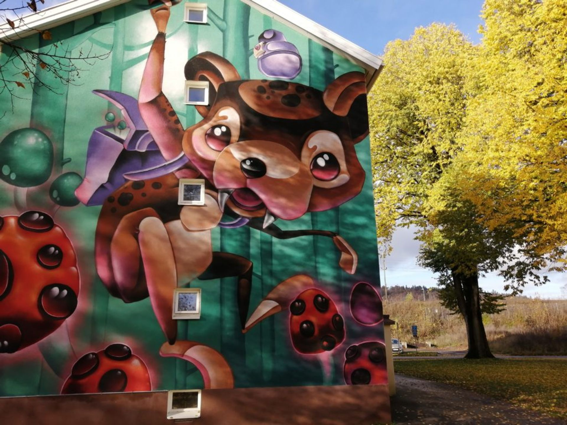 Colourful mural of cute and playful animalistic creature on the side of a residential building.