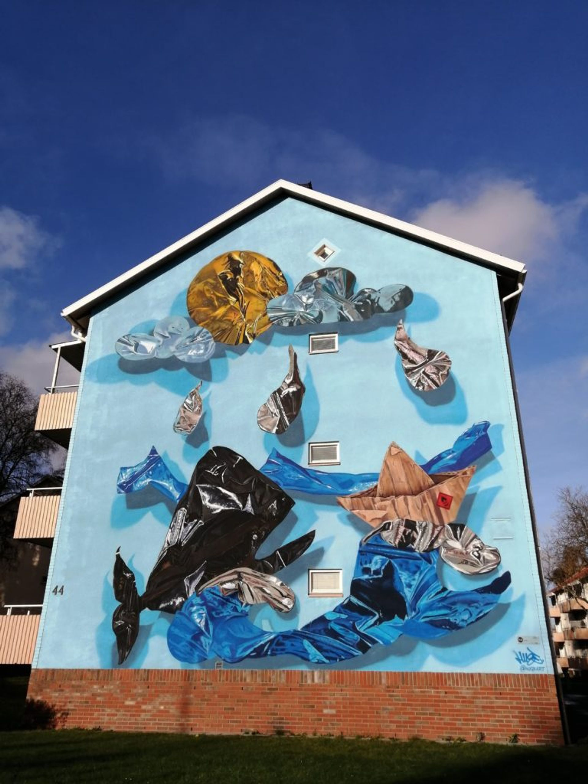 Mural of hyper-realistic balloon whale swimming in litter on the side of a residential building in Borås.