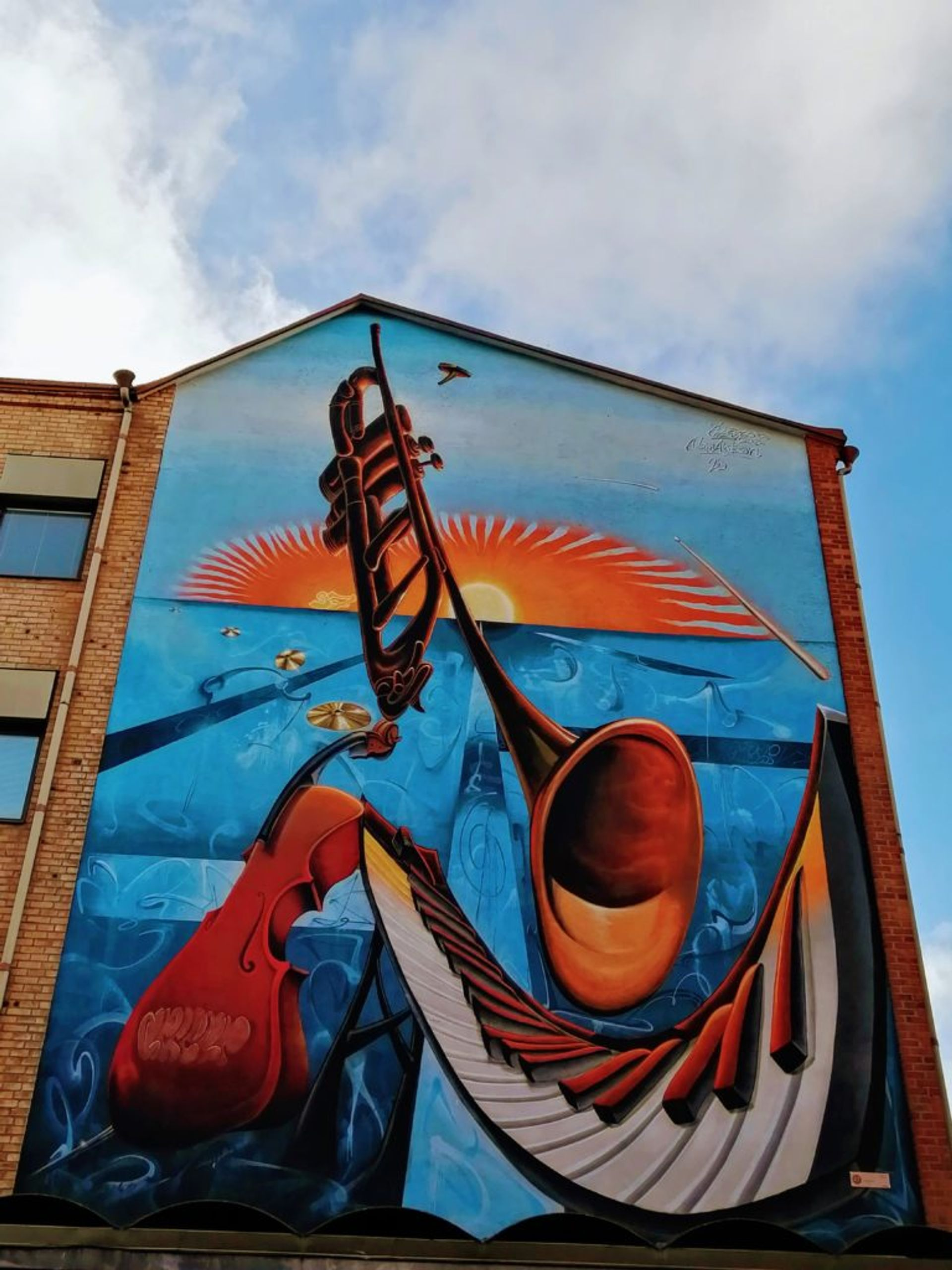 Bright blue and orange mural of musical instruments at sunset on the side of a red-brick building.
