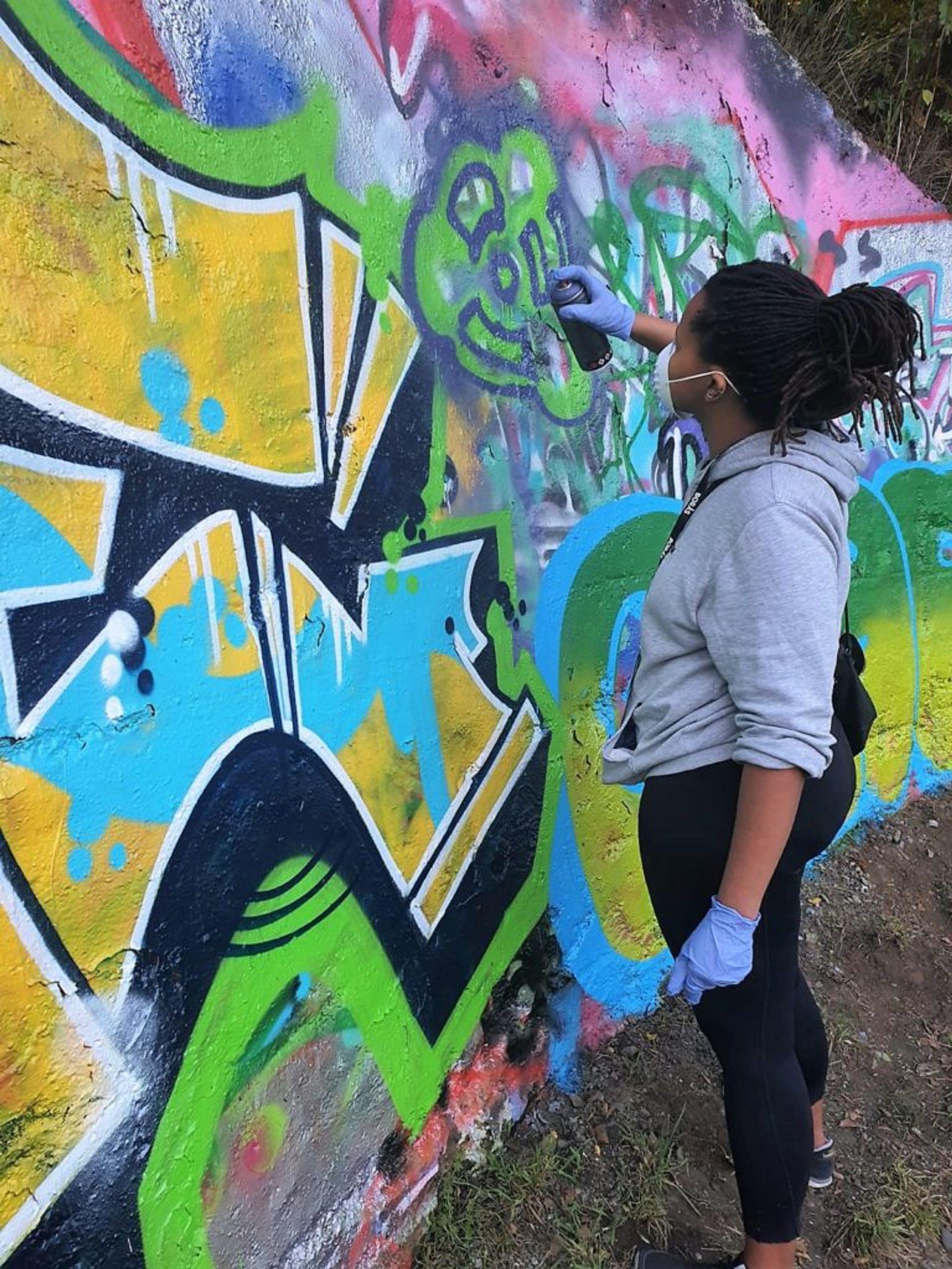 Lusanda spray painting on graffiti wall.