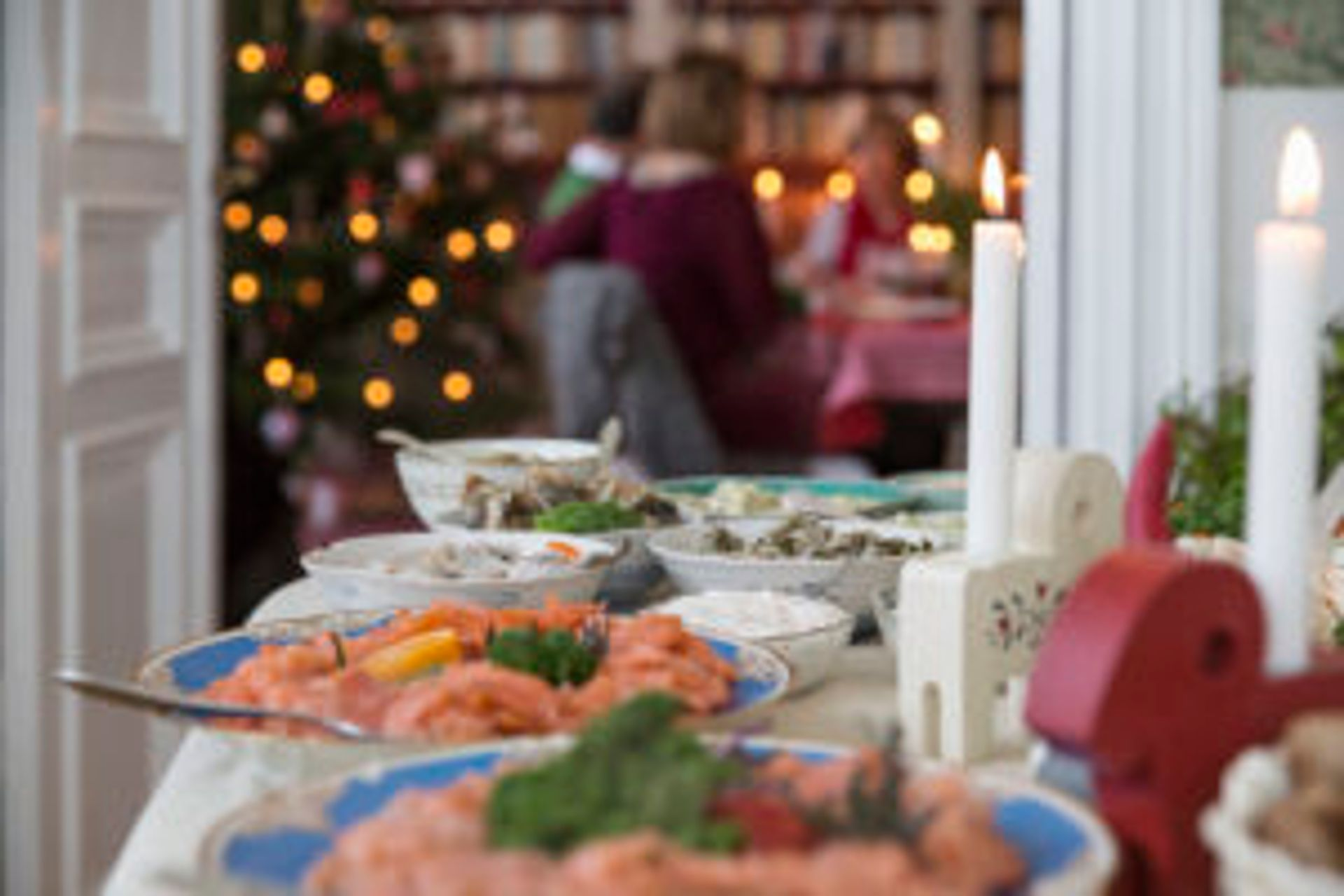 A Swedish Christmas smorgåsbord. A family eating Christmas dinner in the background.