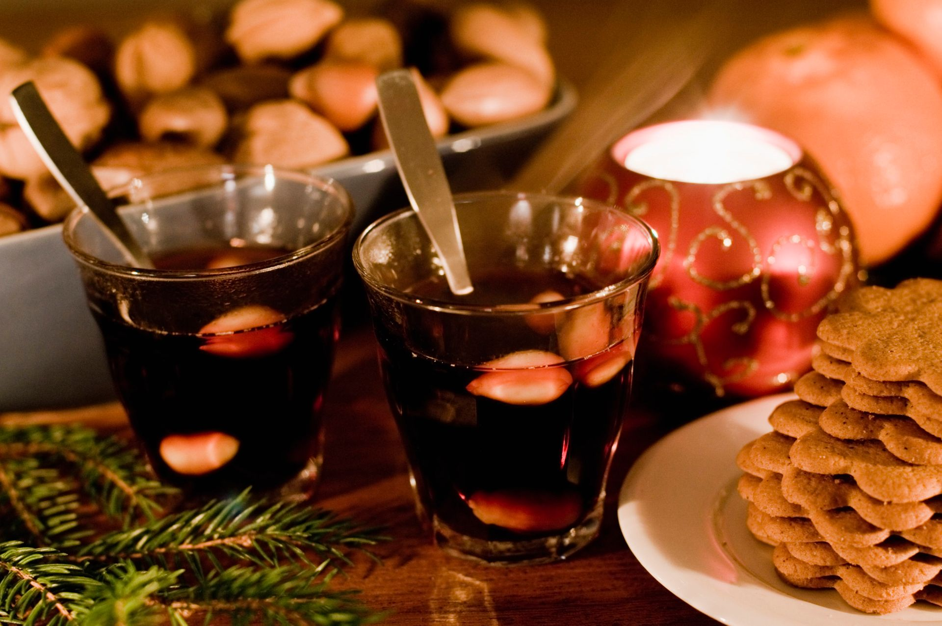 Two small glasses of Swedish mulled wine beside a plate of gingerbred cookies.
