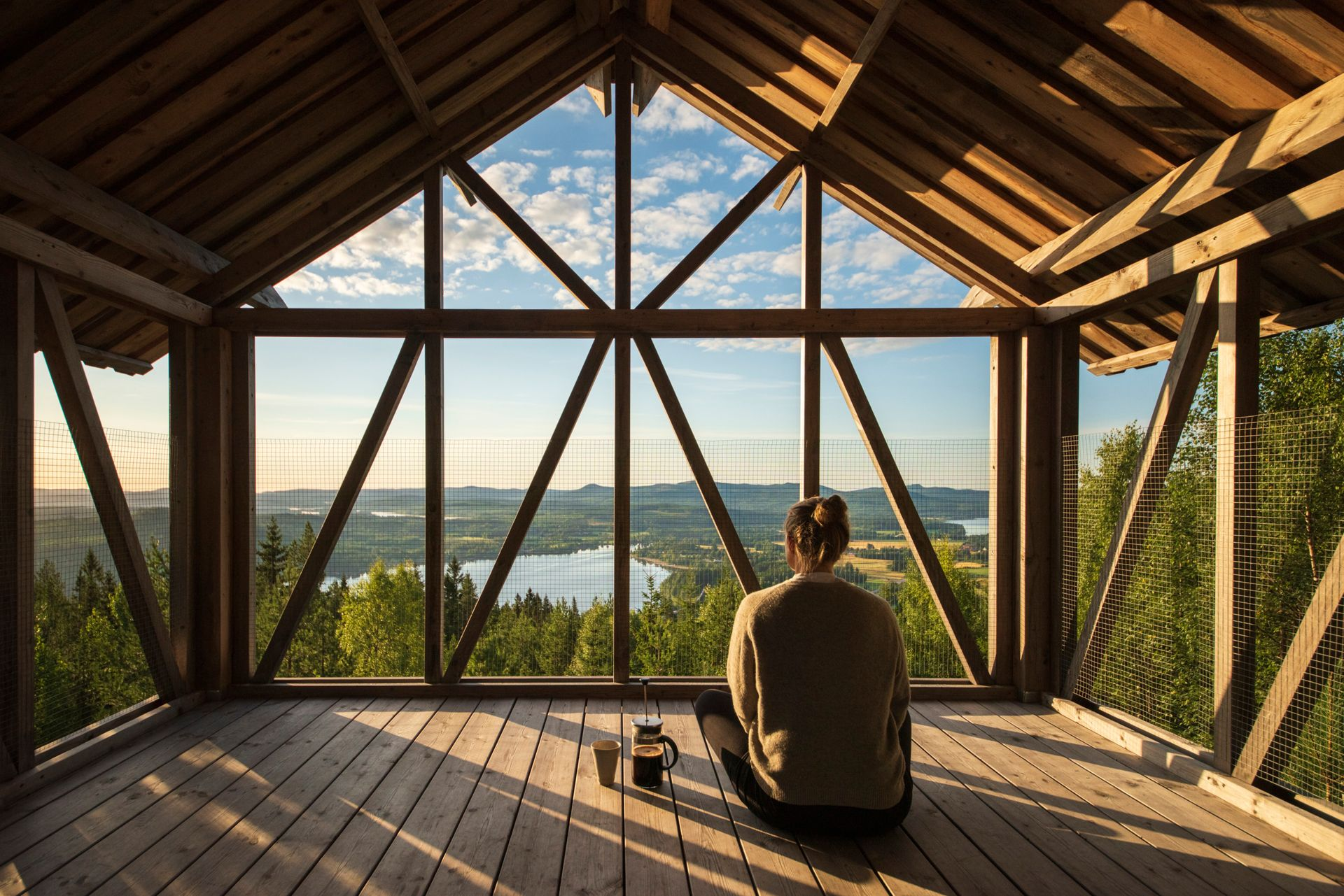 A person sitting inside a wooden construction amongst the treetops a Swedish forrest looking at the view.
