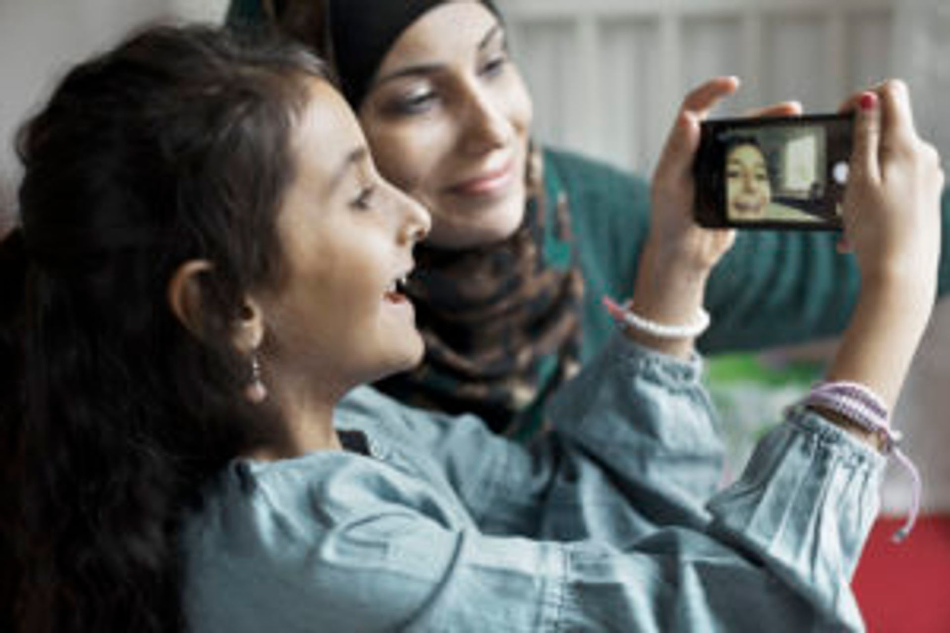 A smiling woman and child taking a selfie together.