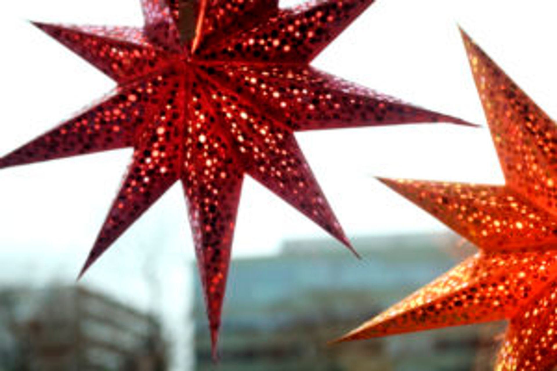 Two red, sparkly paper star decorations hanging in a widow.