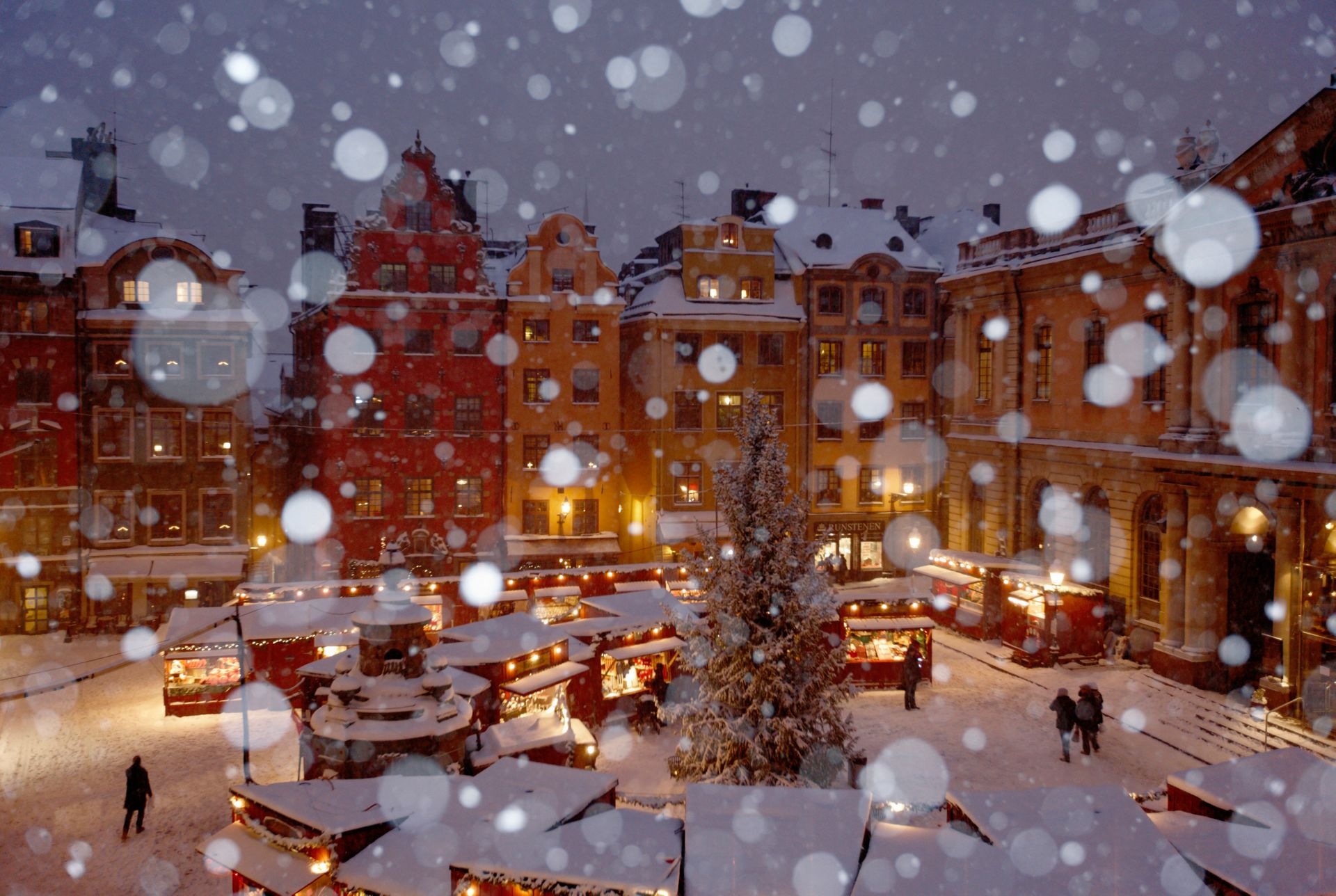 A snowy Christmas market in a square in Stockholm's Old Town.