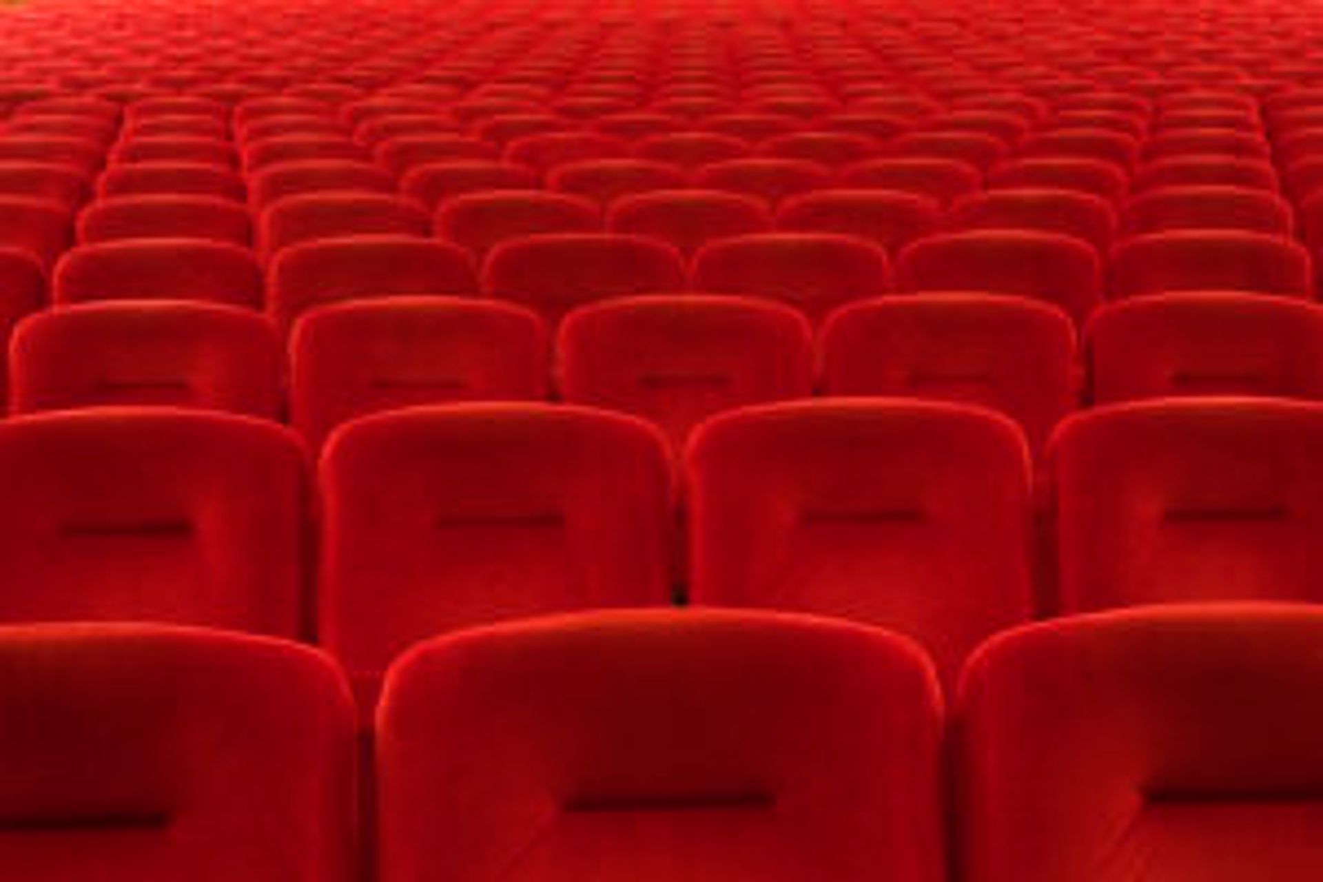 Rows of red velour cinema theatre seats.