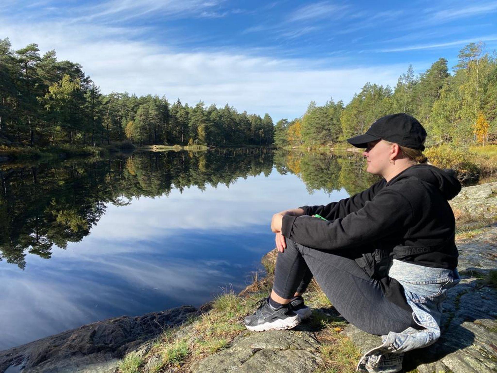 Brooke sitting alongside a lake surrounded by trees
