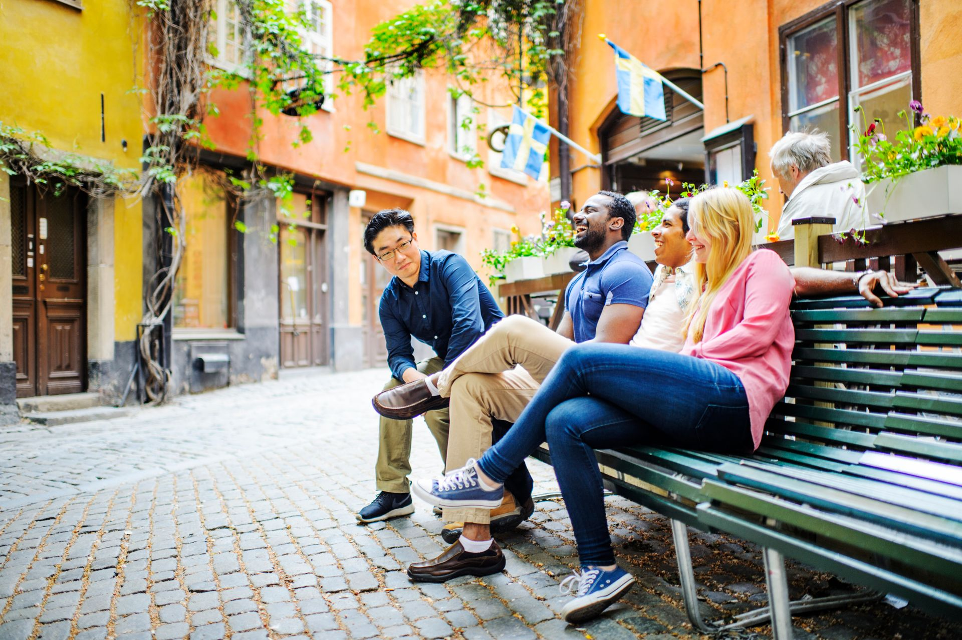 Friends sitting on a bench in Stockholm's Old Town.
