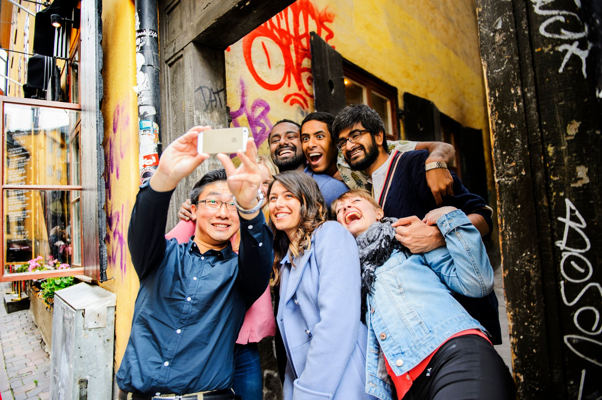 A group of international students taking a group selfie in Stockholm's Old Town.