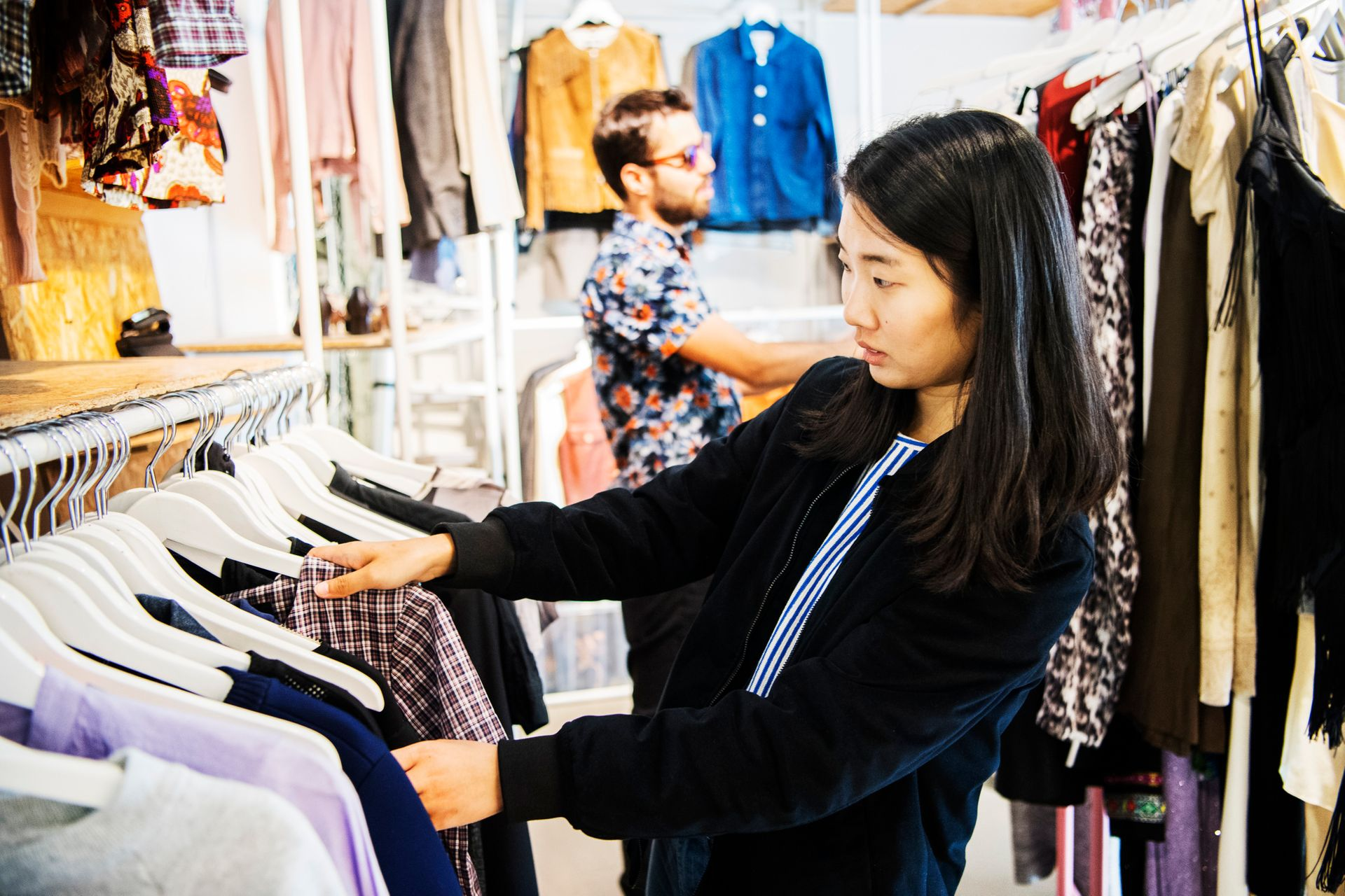 A woman browsing clothes in a vintage shop.