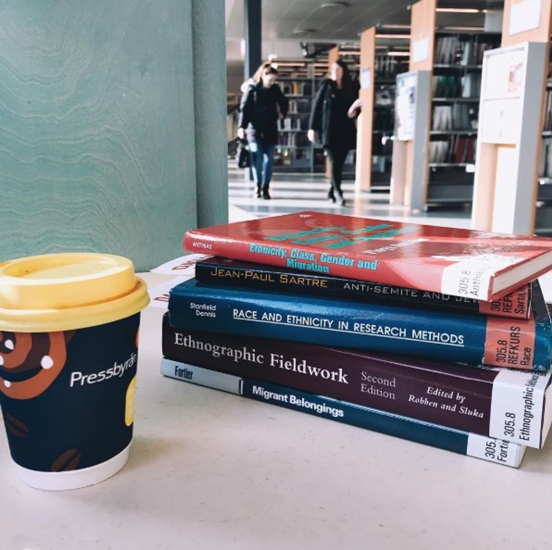 Close-up of university books and a cup of coffee.