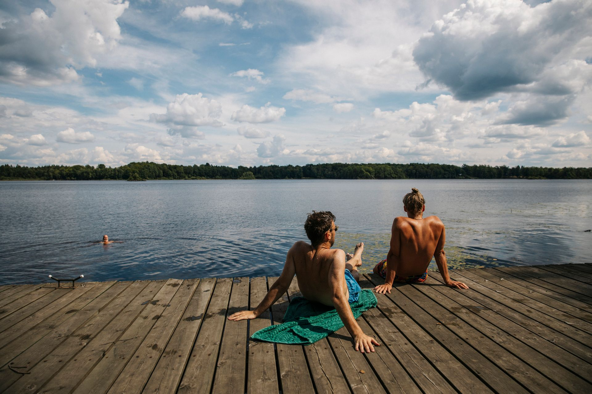 By the lake , two men tanning