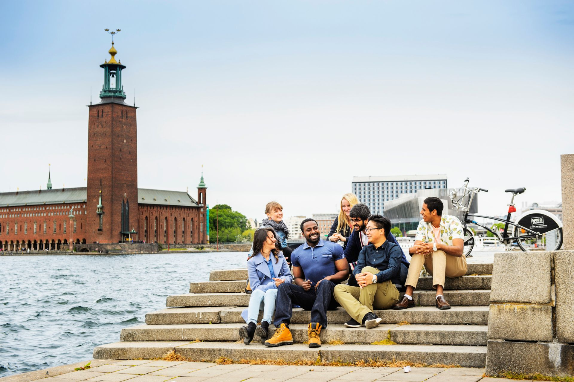 A group of students sitting on stairs, with the Stockholm City Hall in the background.