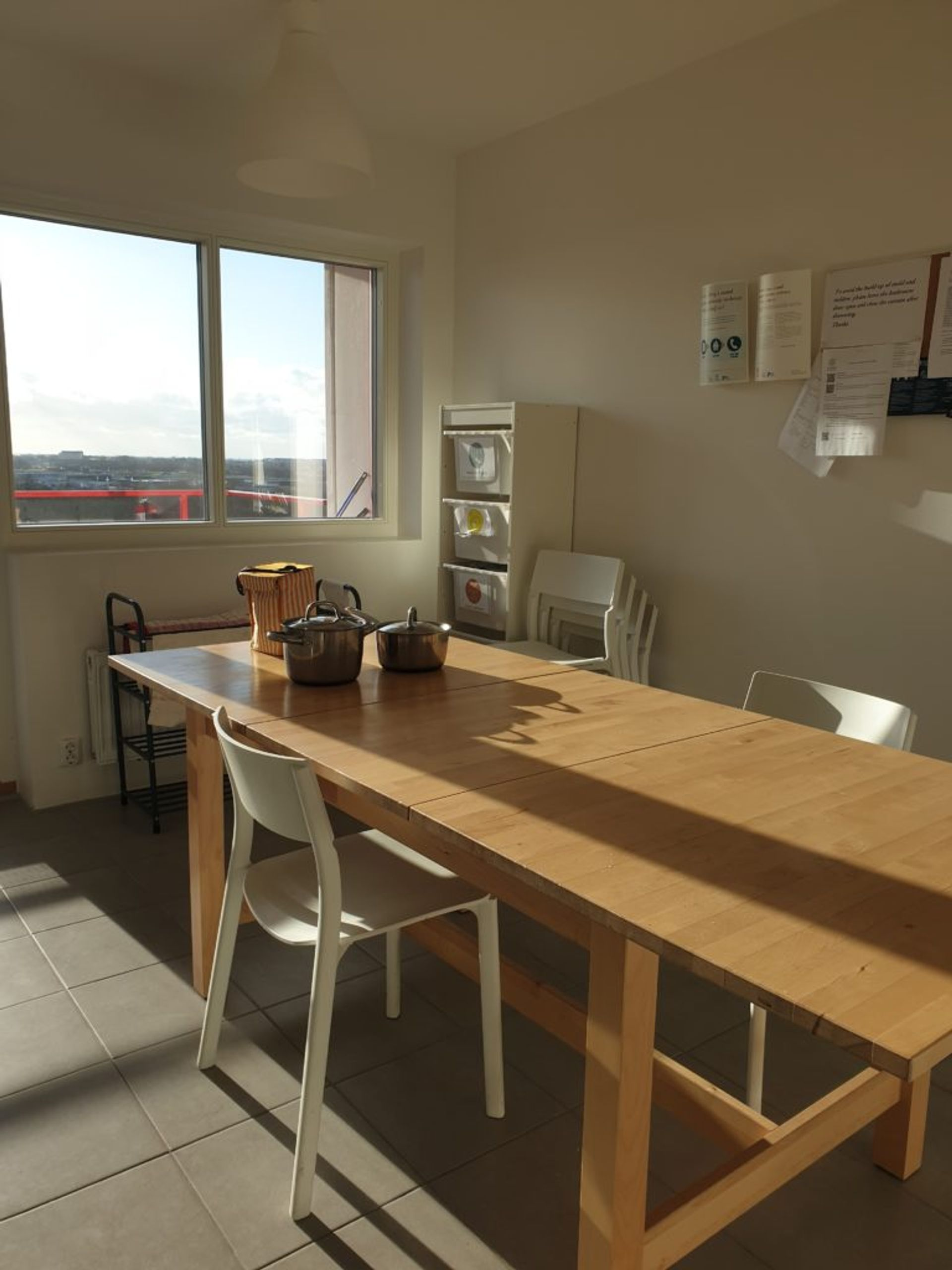 Wood table with white chairs with sun shining through window