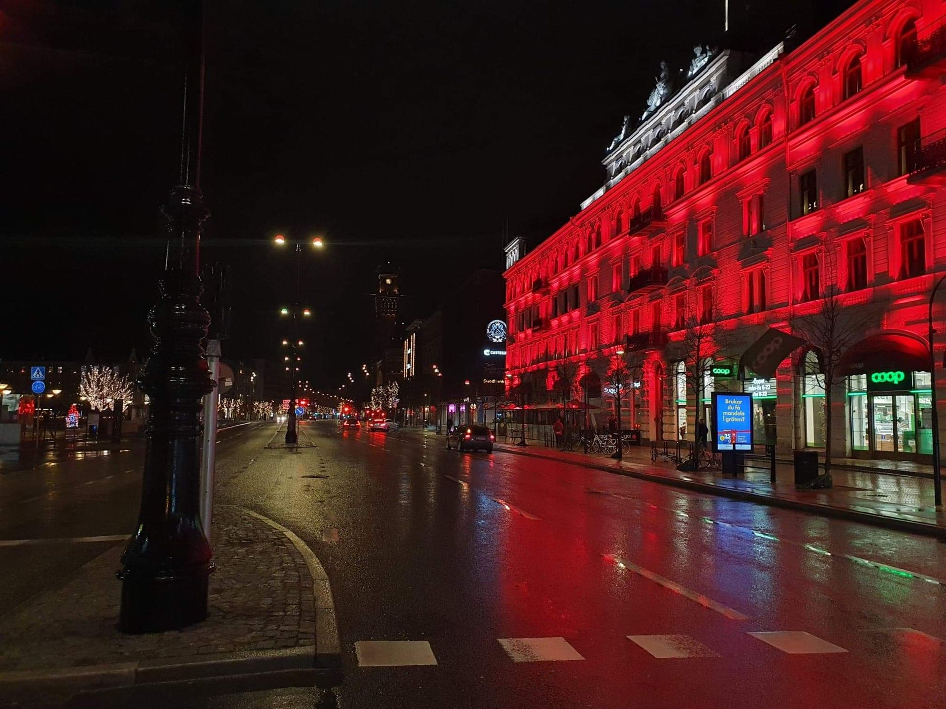 Dark evening, a wet glistening street in front of a building with bright red lights