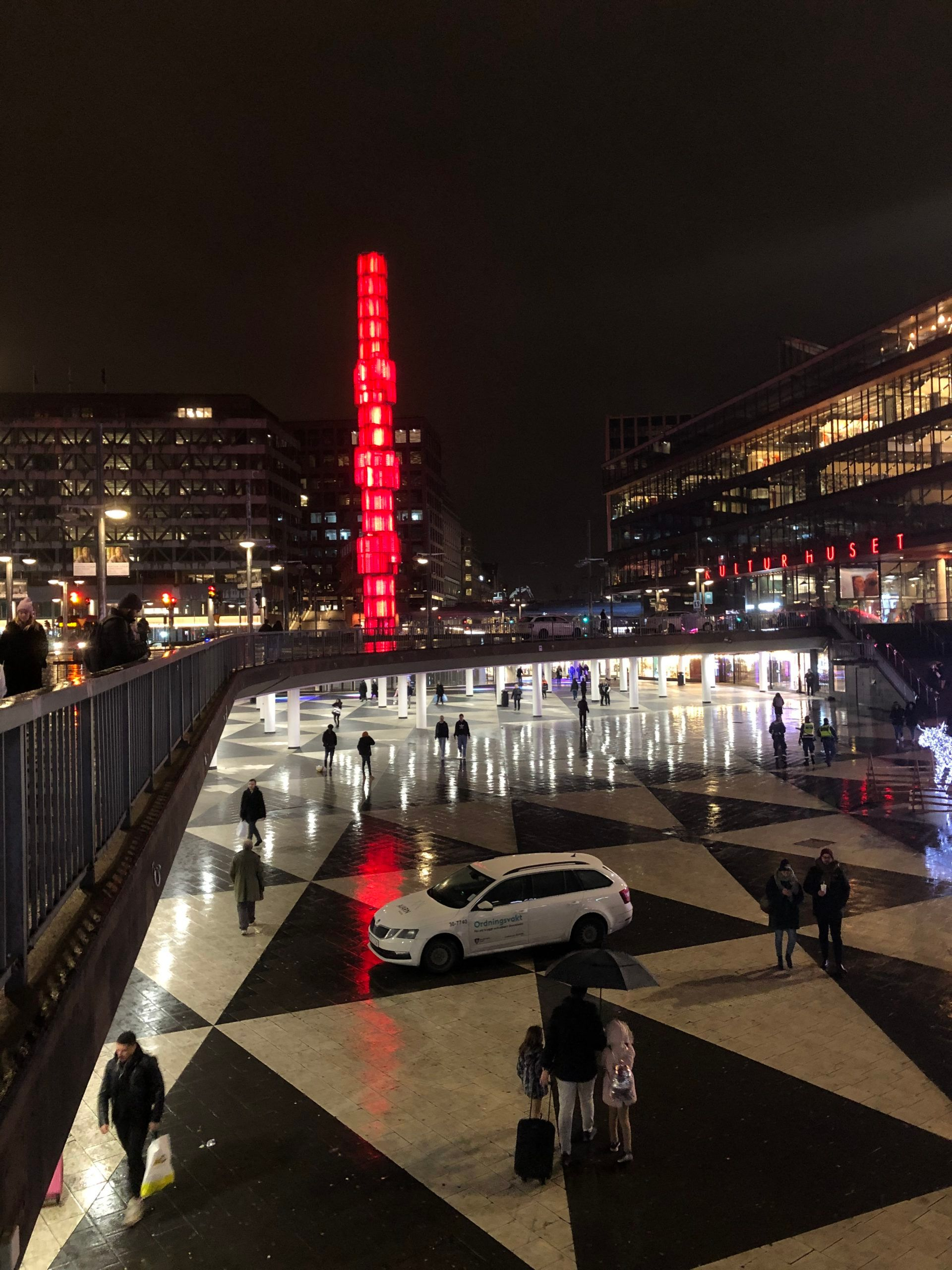 A tall tower building lit fully in red lights onto a shiny, black and white triangle designed pavement, behind a bridge reflecting scattered lights. Pedestrians walking under the bridge and a car parked in front.