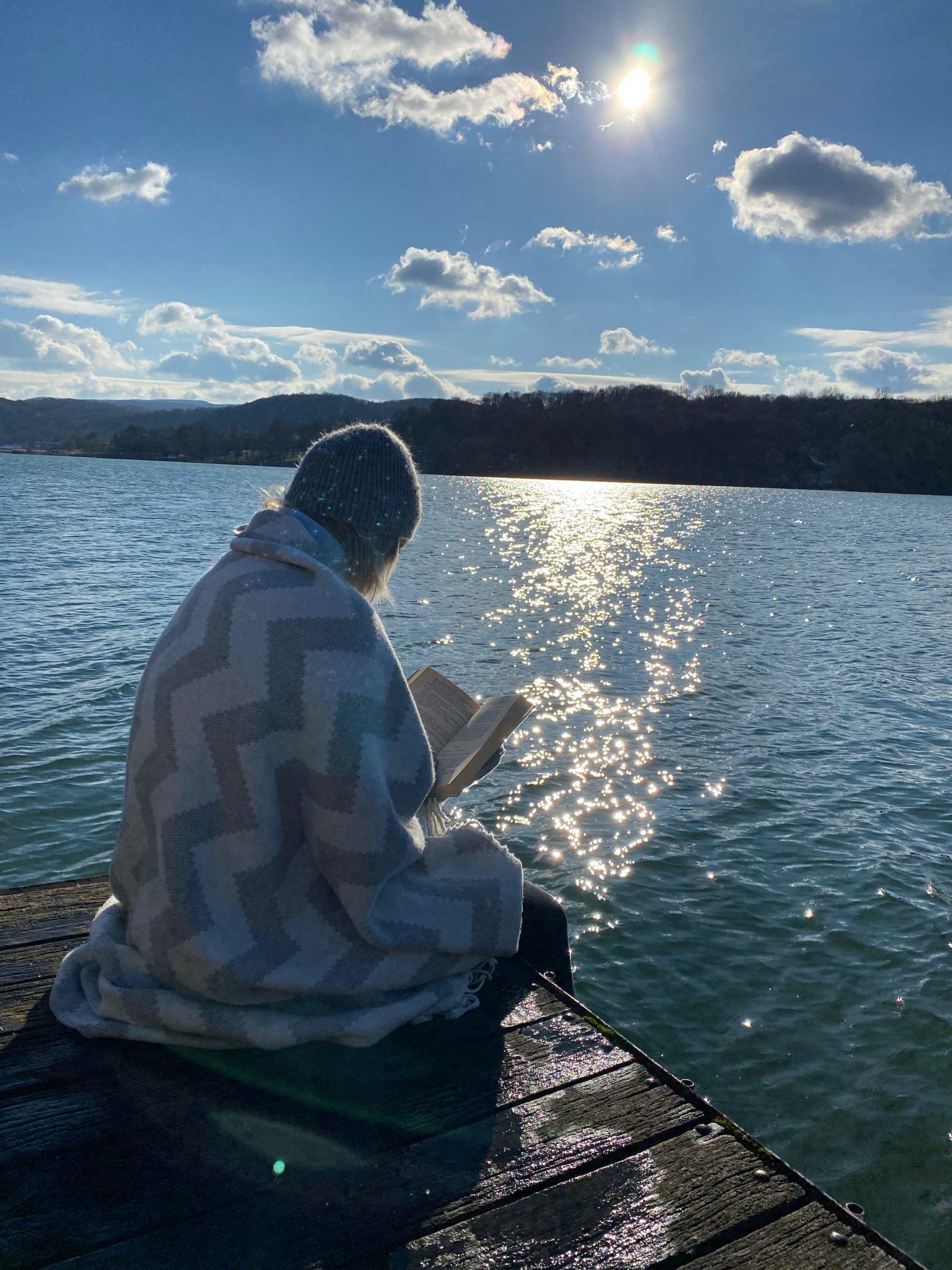 Sara sitting alongside a lake and reading