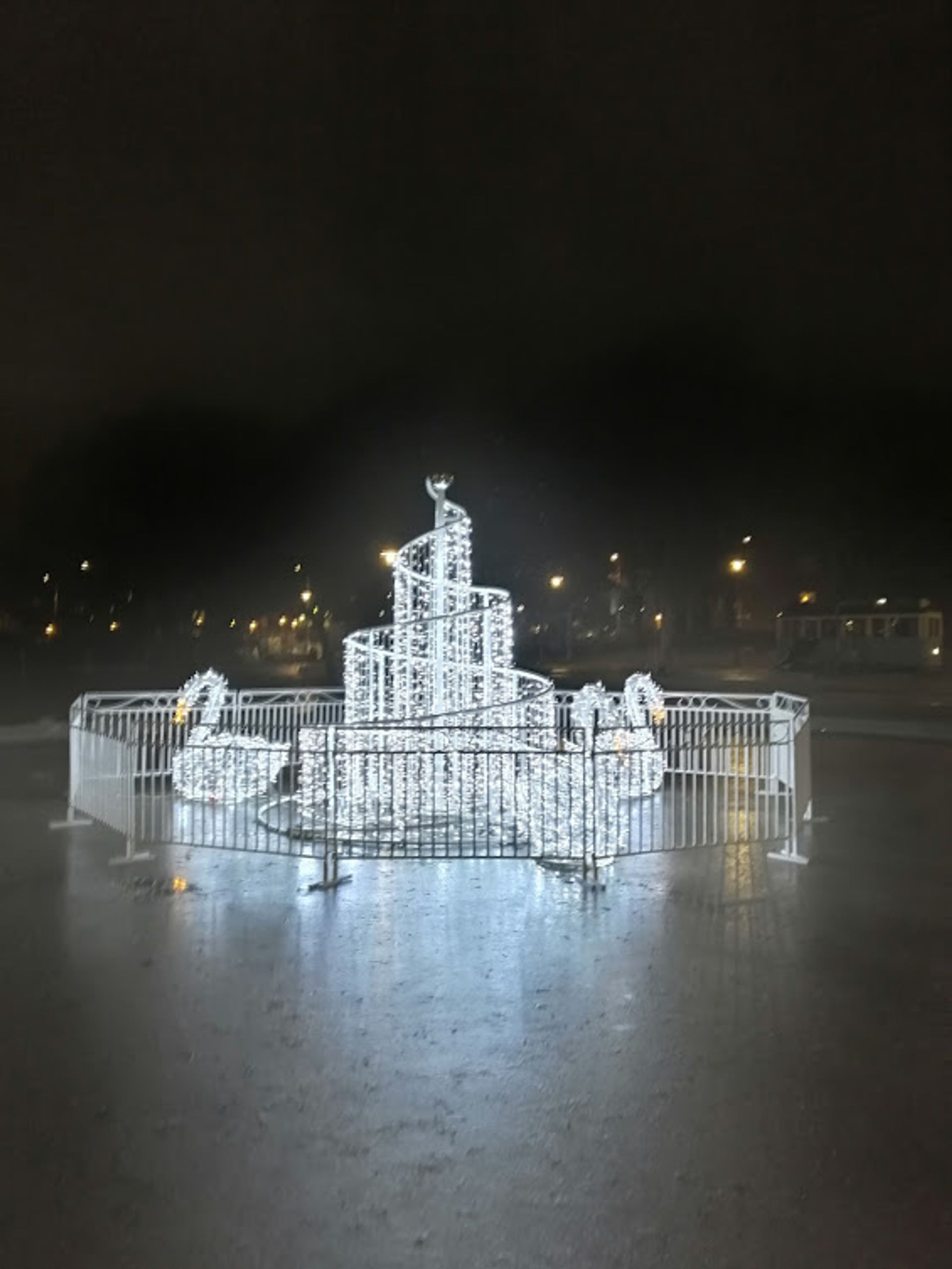 A light sculpture of swans around a spiral of fairy lights