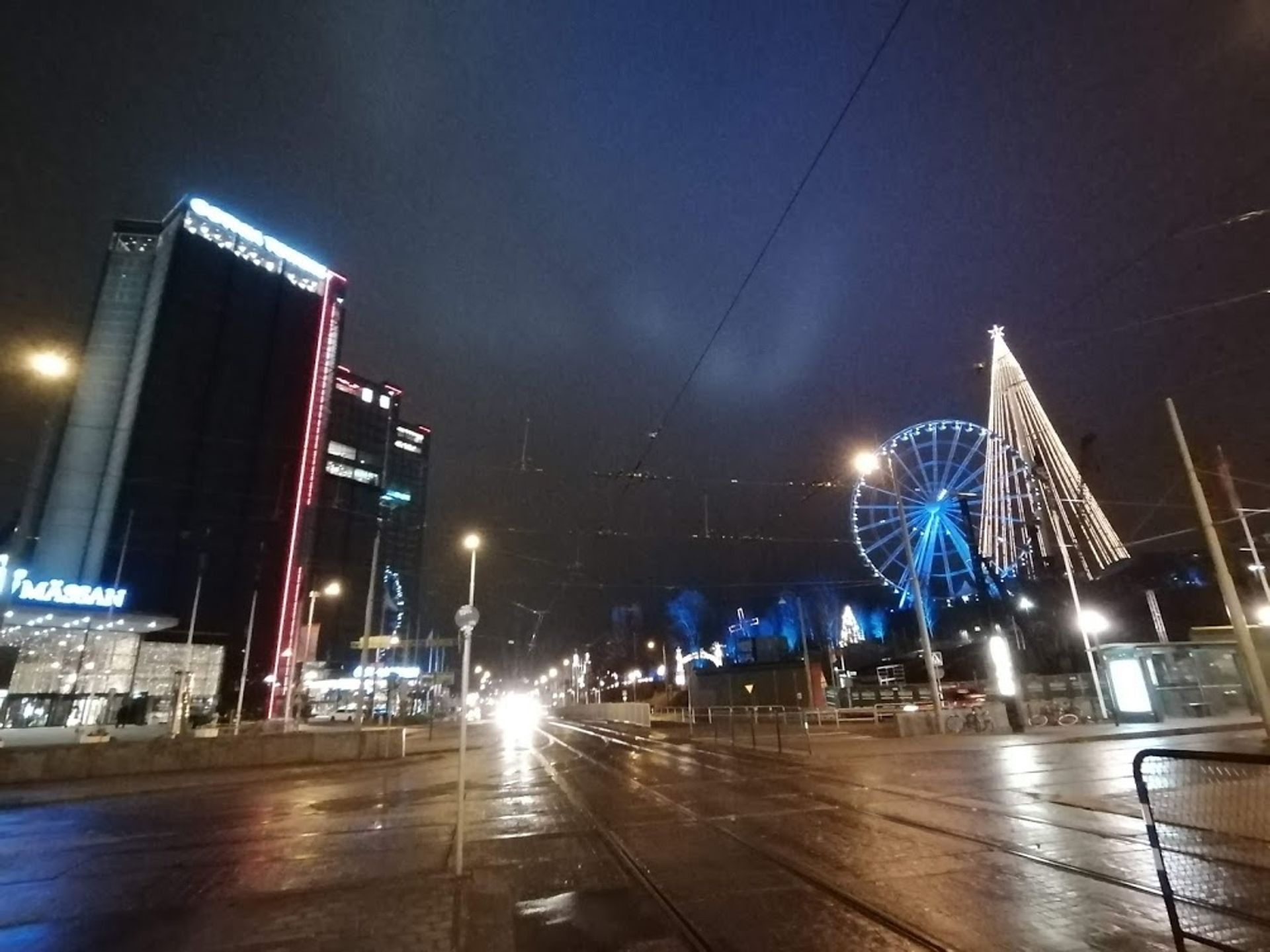 lights reflecting on a glistening street, with a lit up ferris wheel and tree light scuplture in the background