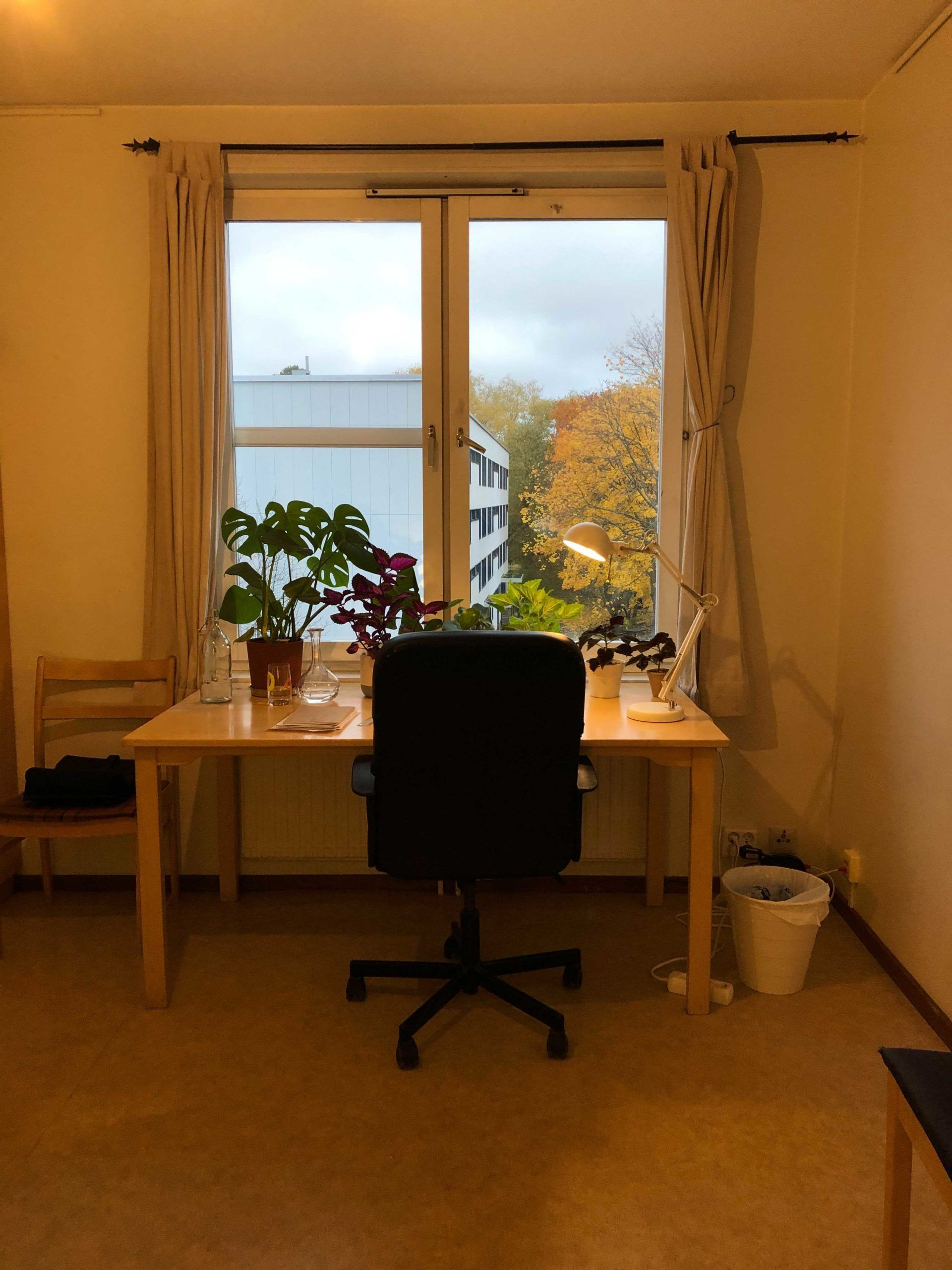 Desk and chair sit in front of large window with light shining through