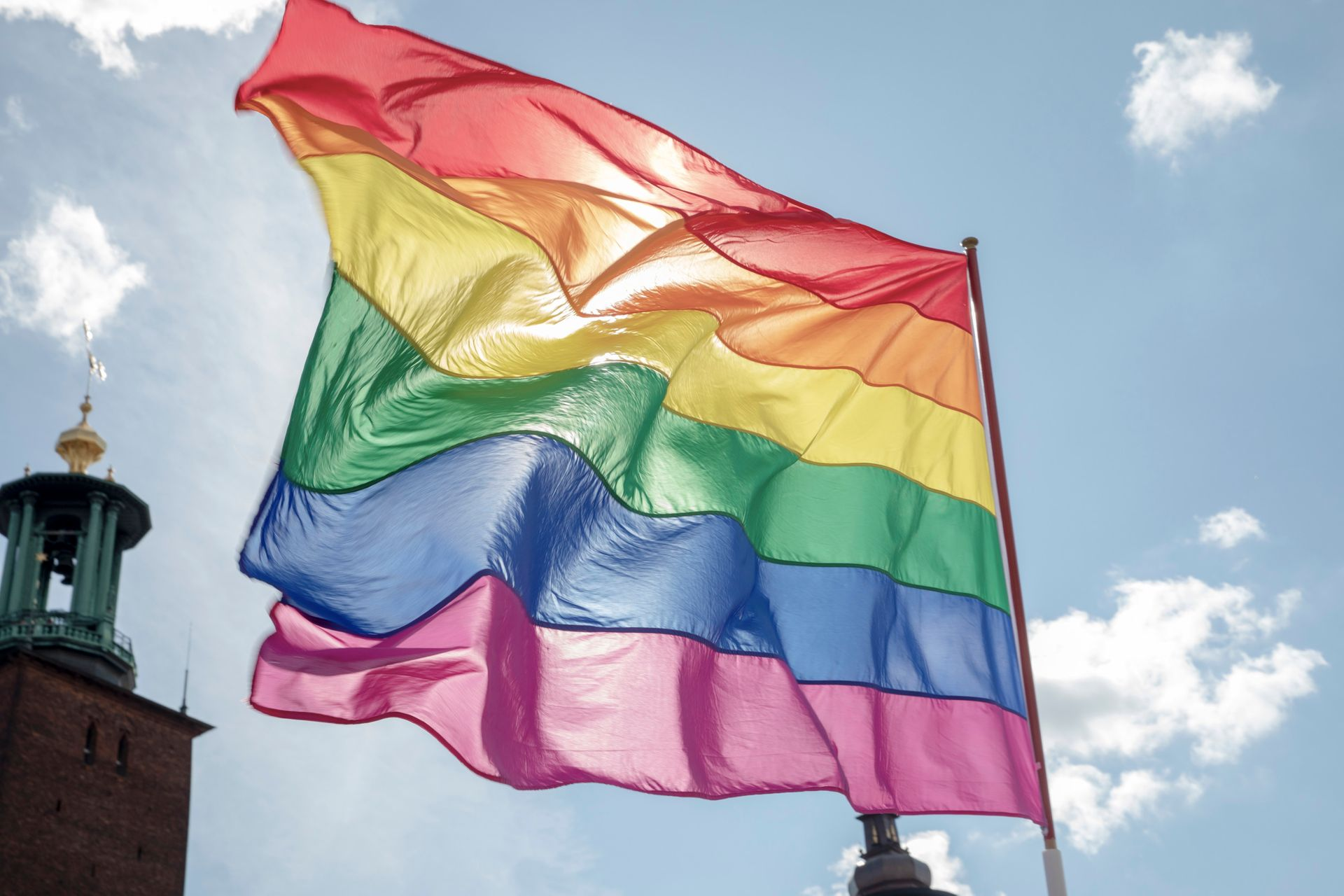 A rainbow flag flutters in the wind. The tower of Stockholm city hall in the background.