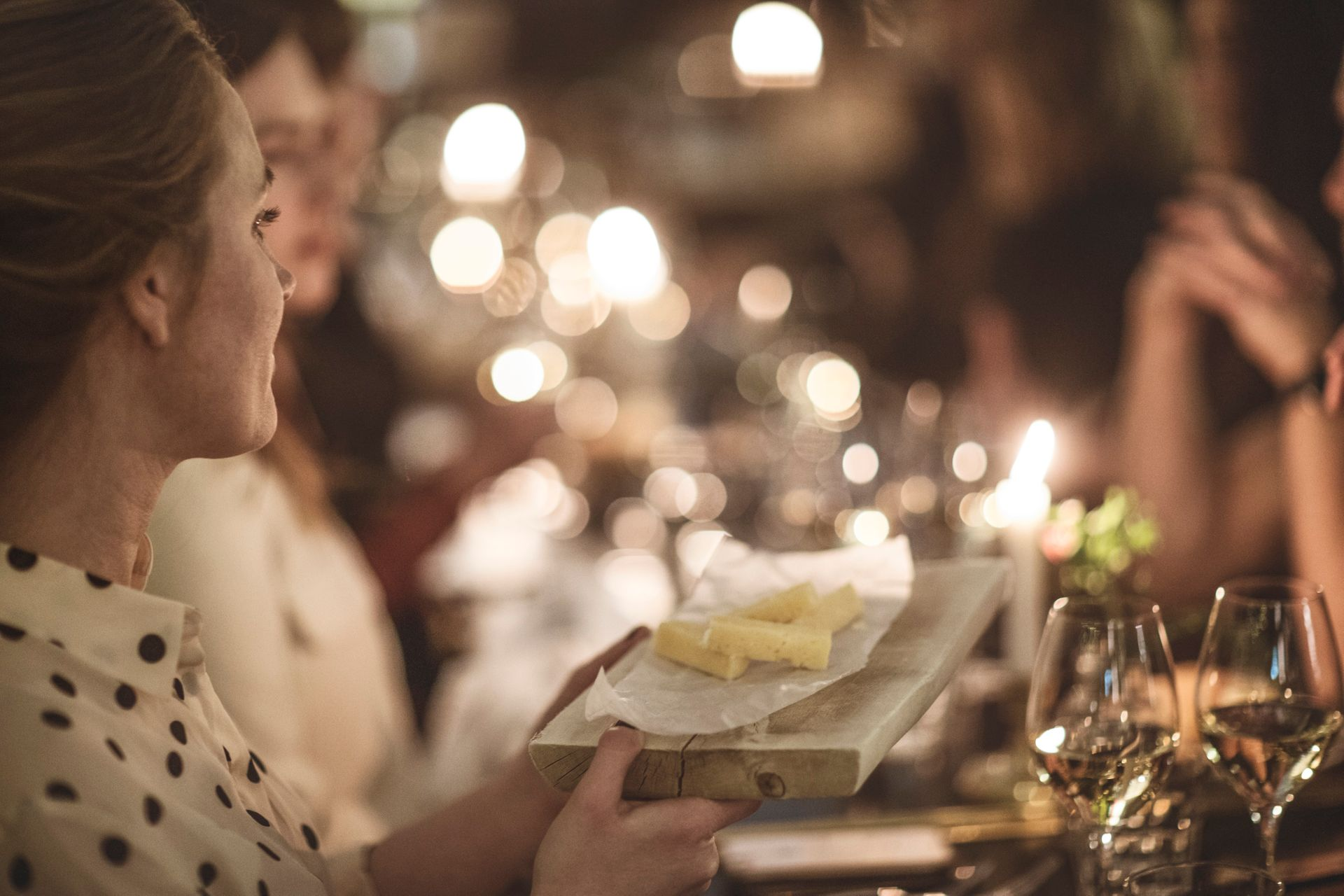 A woman holding a cheese board and in the blurry background you see people and lights