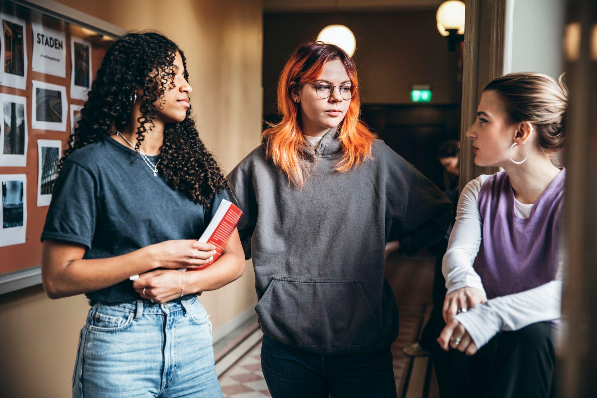 Three teenage girls stand in a hallway, talking.