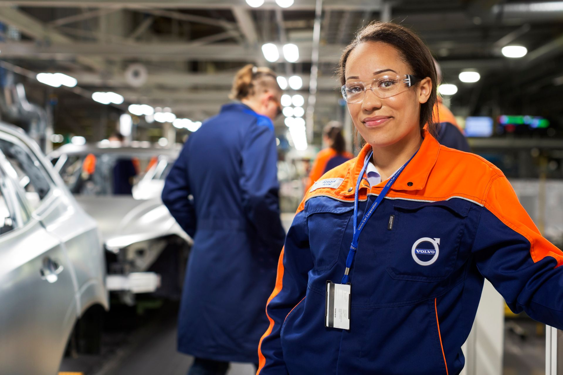 A proud woman engineer standing in front of a car wearing a Volvo uniform