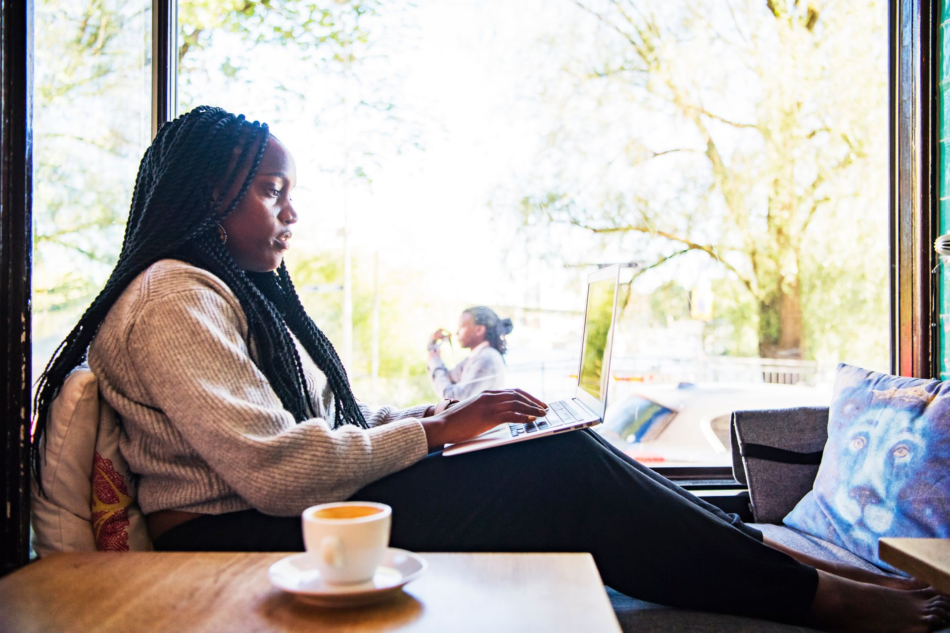A woman is sitting inside by a window with a cup of coffee, typing on a laptop in her lap.